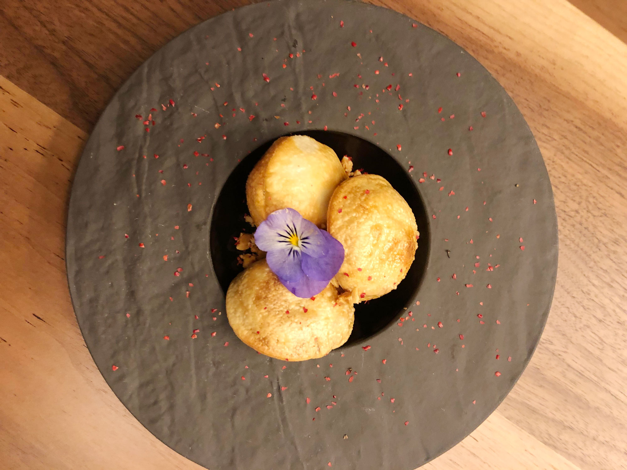 The round fried balls of crispy foie gras PB&J sit in a bowl topped with a purple flower.