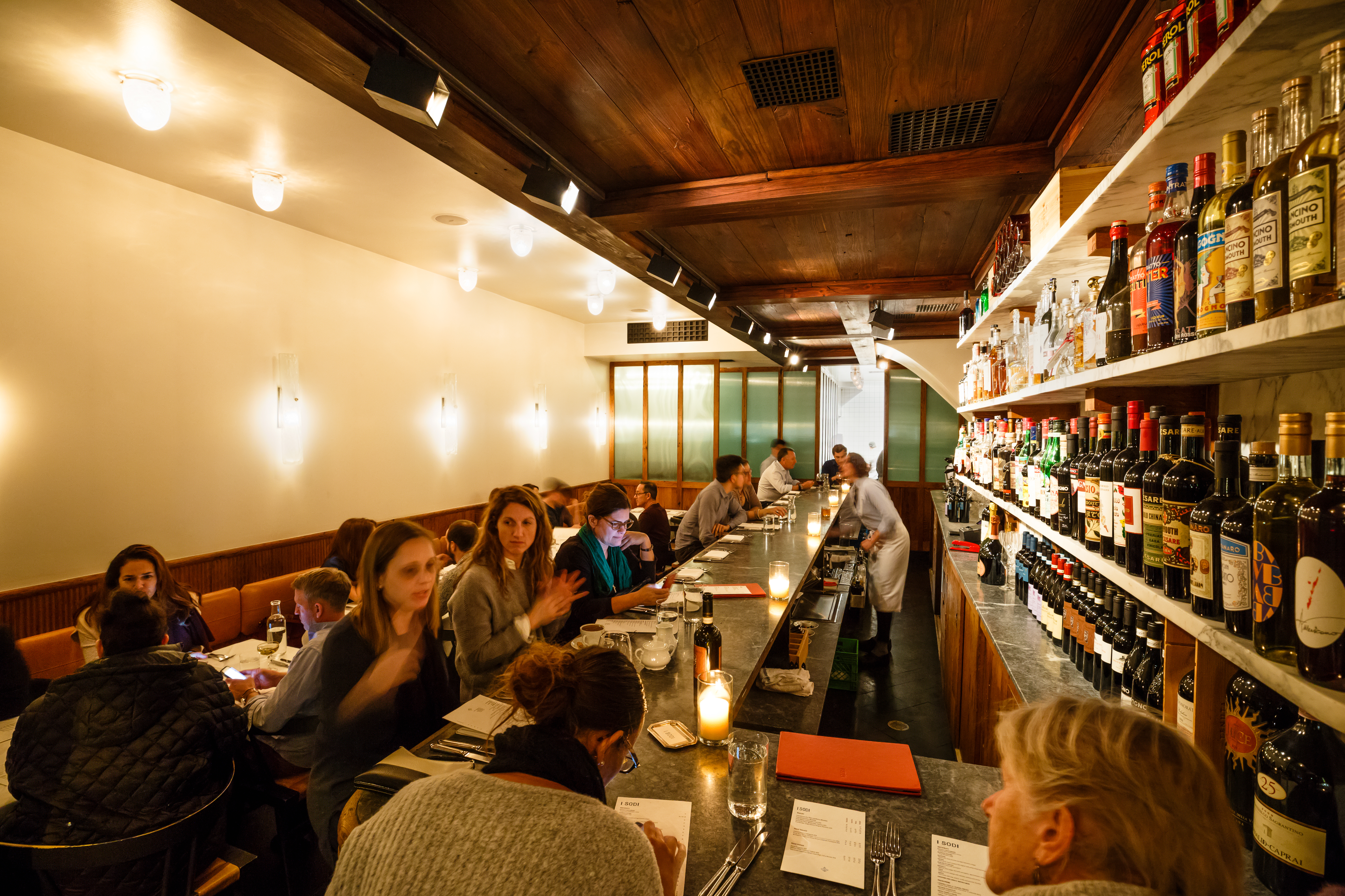 Customers dine at a busy I Sodi, with one wall lined with wine bottles