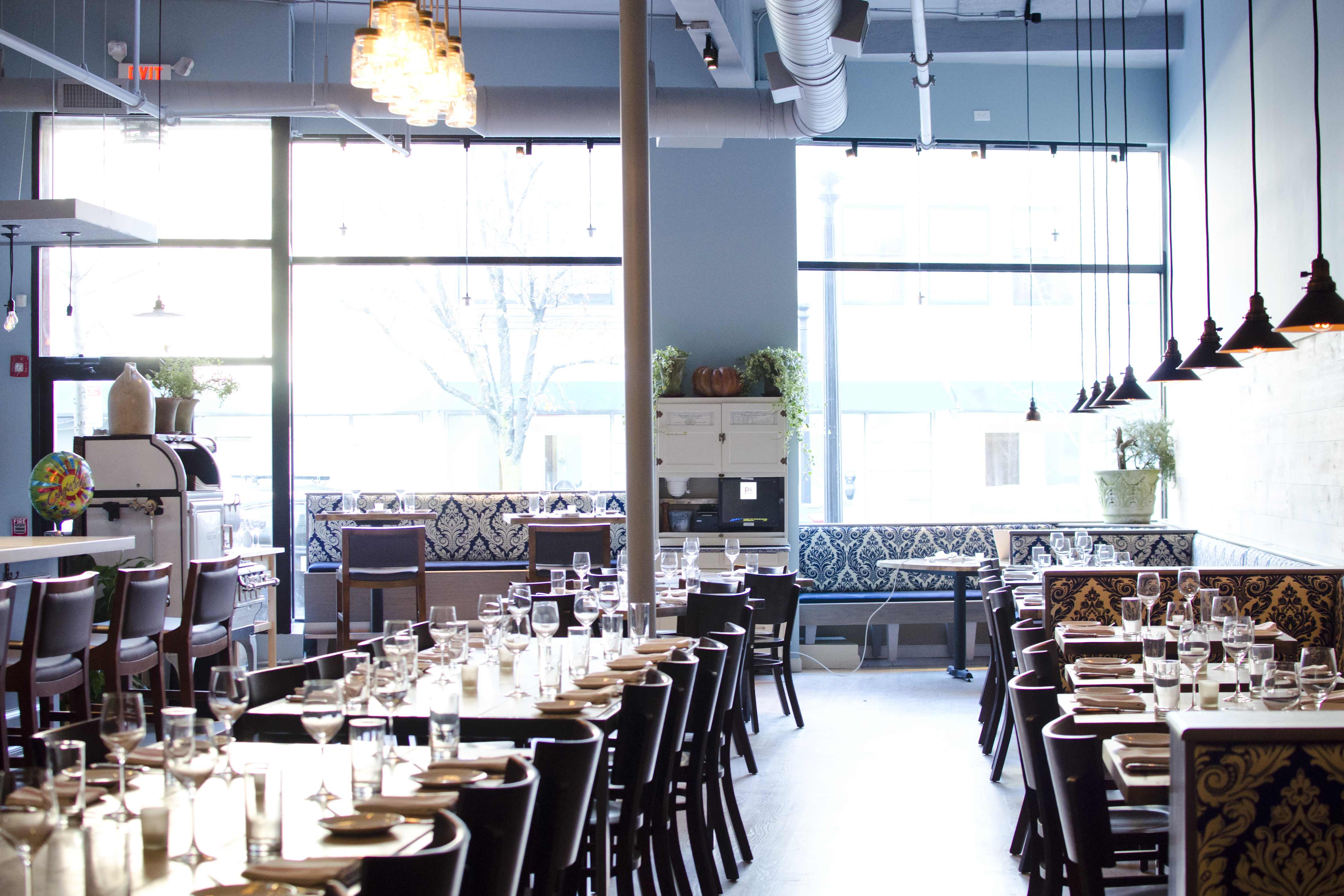 A restaurant interior is photographed during the day, toward the large front windows, lit up by sun. The walls are light blue; the space is rustic but polished.