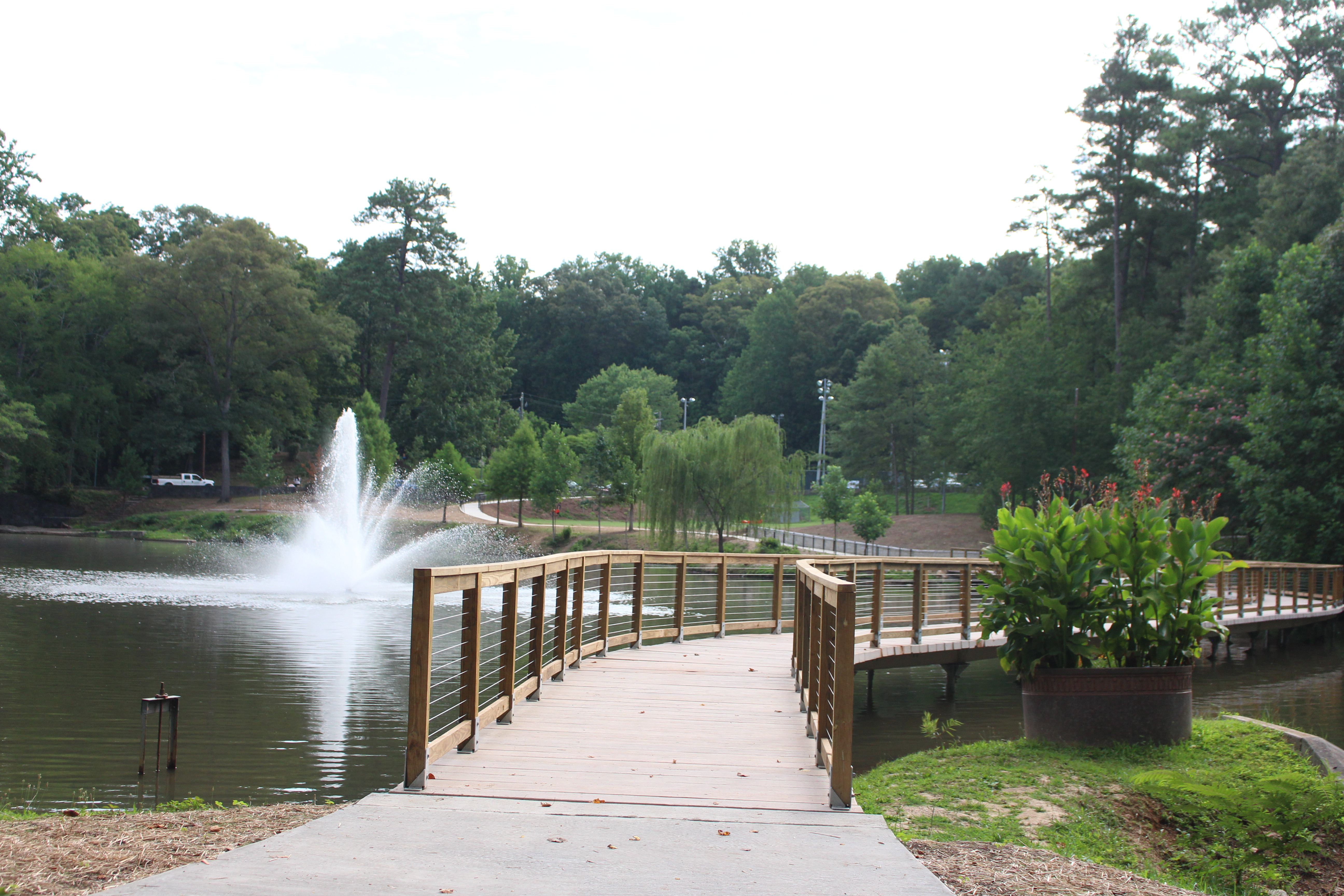 A boardwalk across a lake with a fountain.