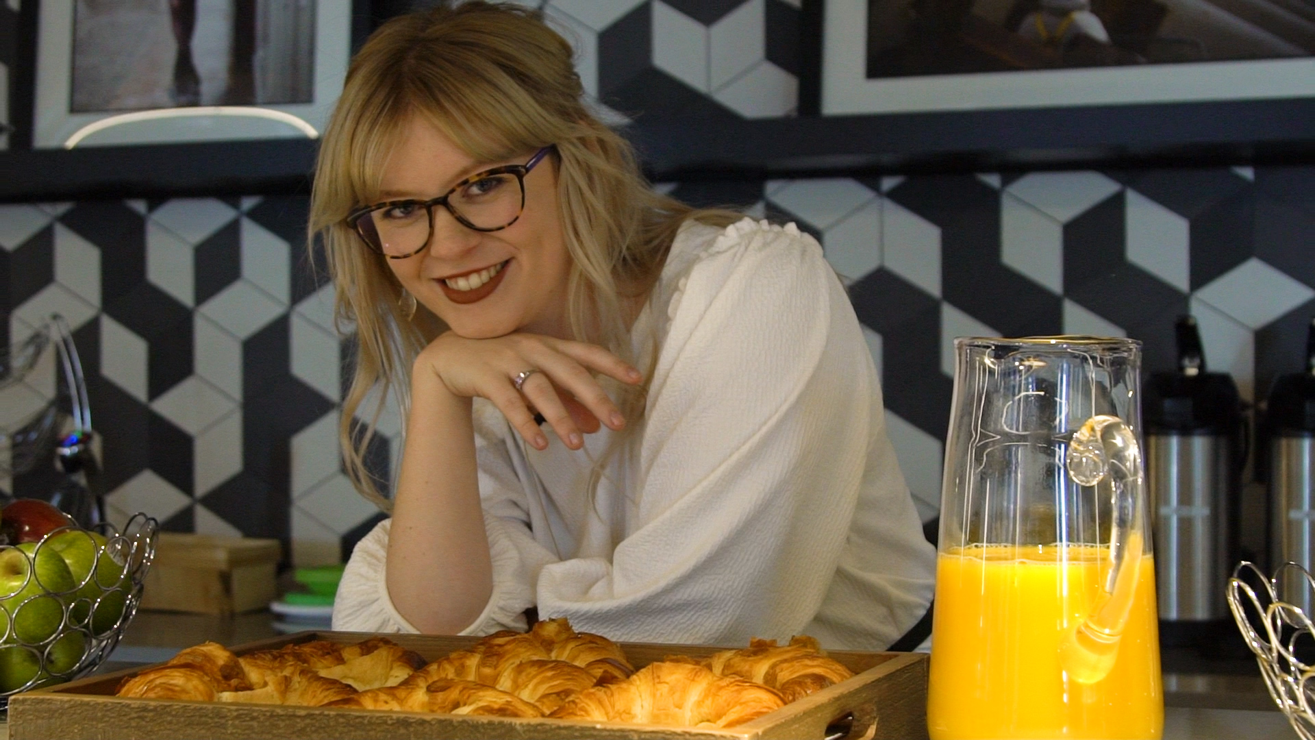 Rebecca Jennings in glasses over a tray of croissants