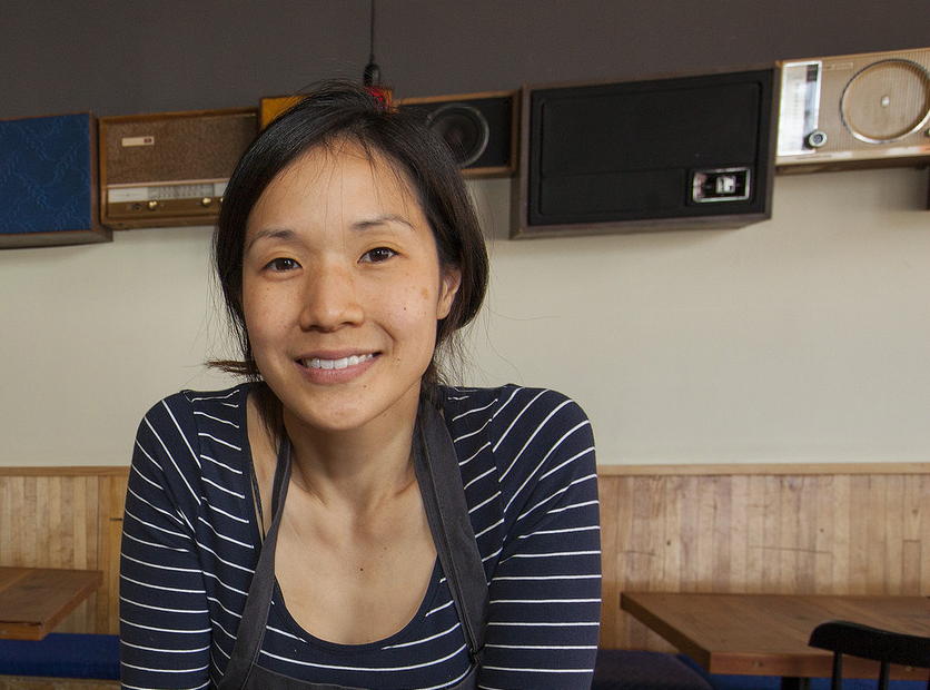 A dark-haired woman leaning against a bar and smiling.