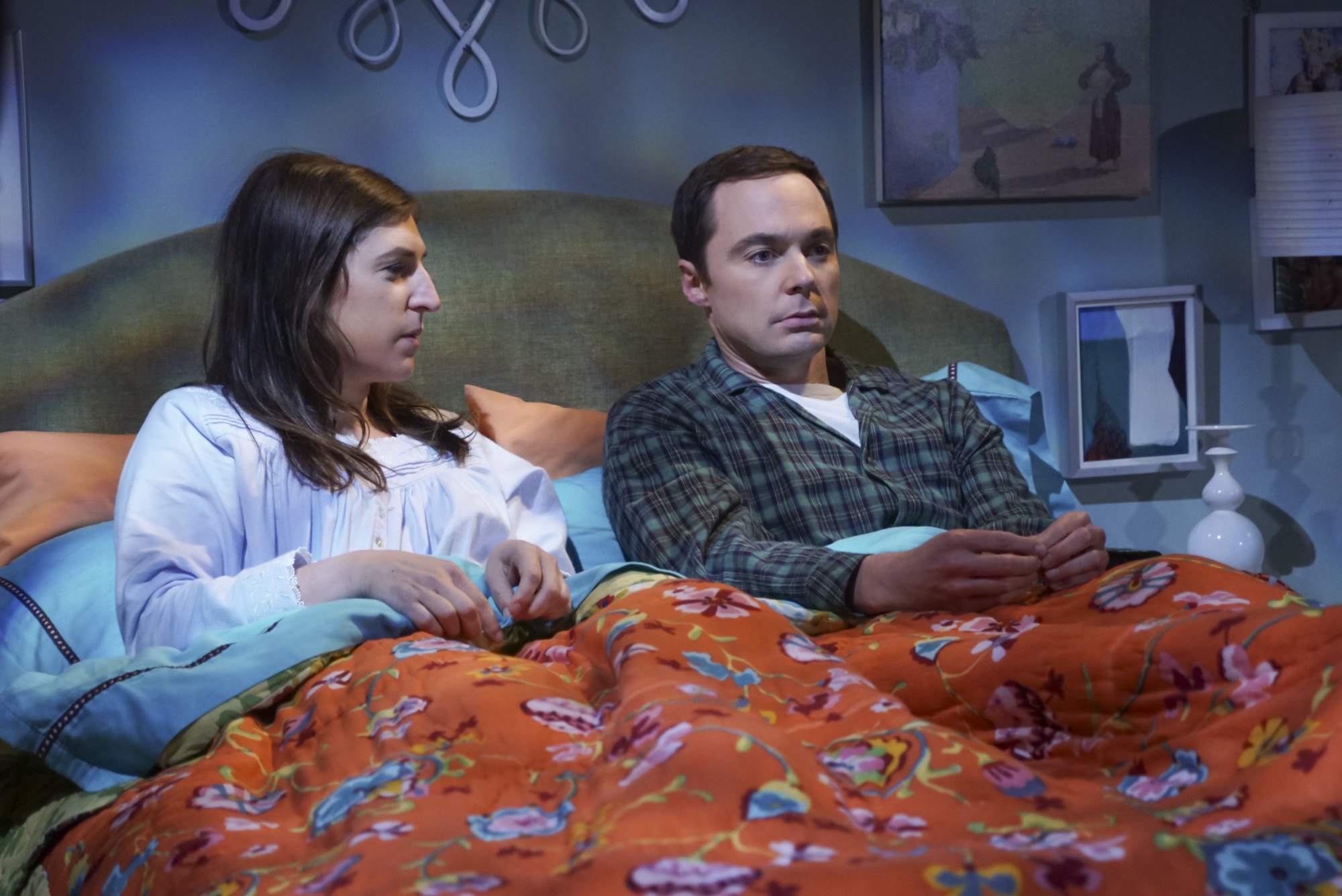 """Two actors from the CBS TV show """"The Big Bang Theory"""" are sitting up in their bed."""
