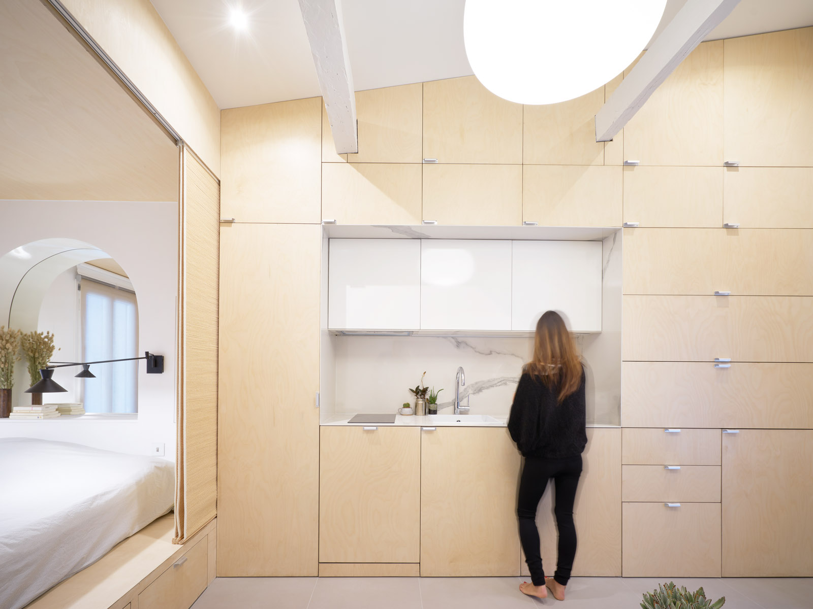 Interior of small studio apartment with a wall of lightwood cabinets and a small kitchen counter, with a bed on a pedestaled unit to the left of it. A woman stands at the sink.