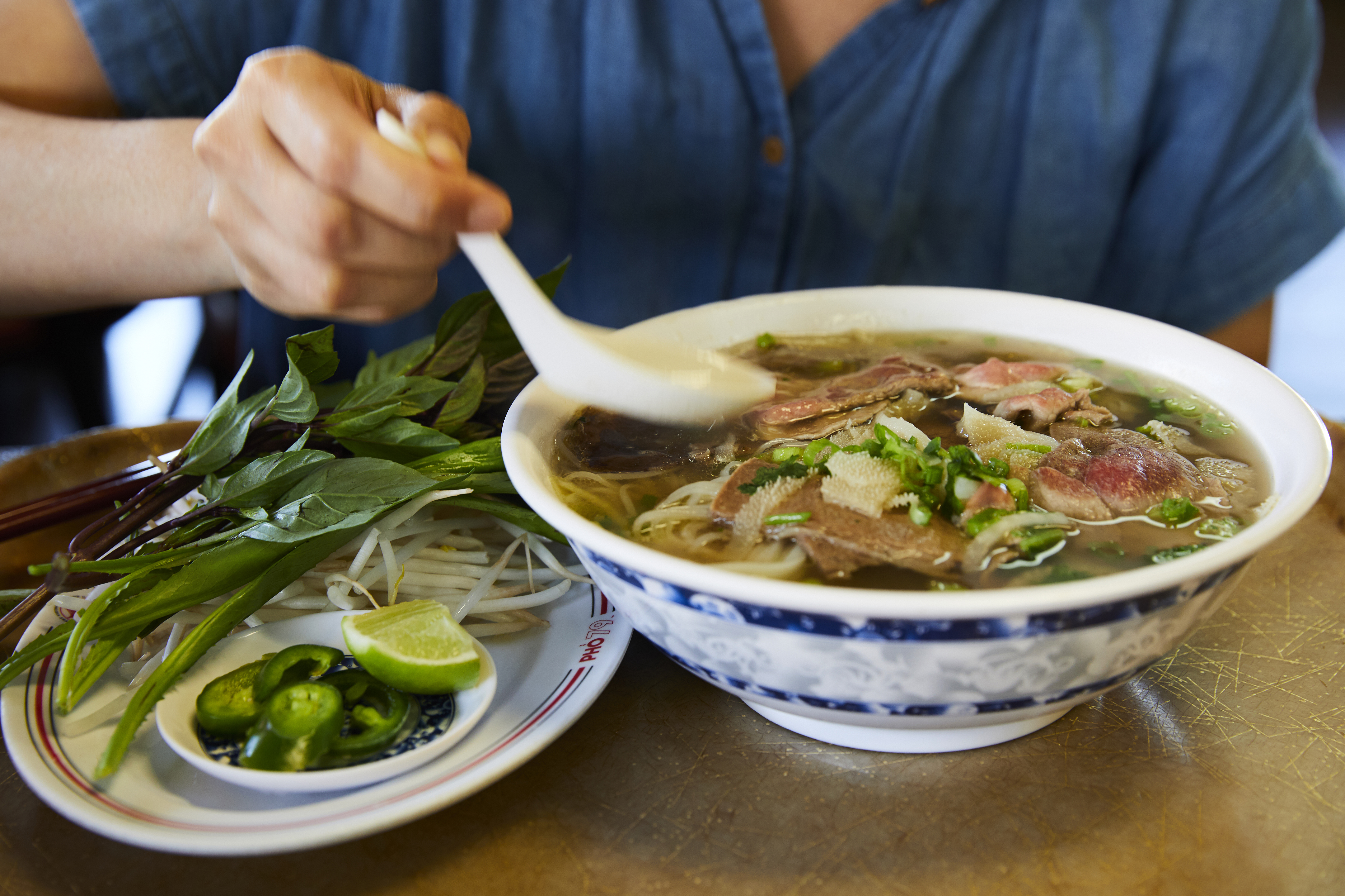 A diner digging into a bowl of steaming hot beef noodle soup at Pho 79 in Garden Grove.