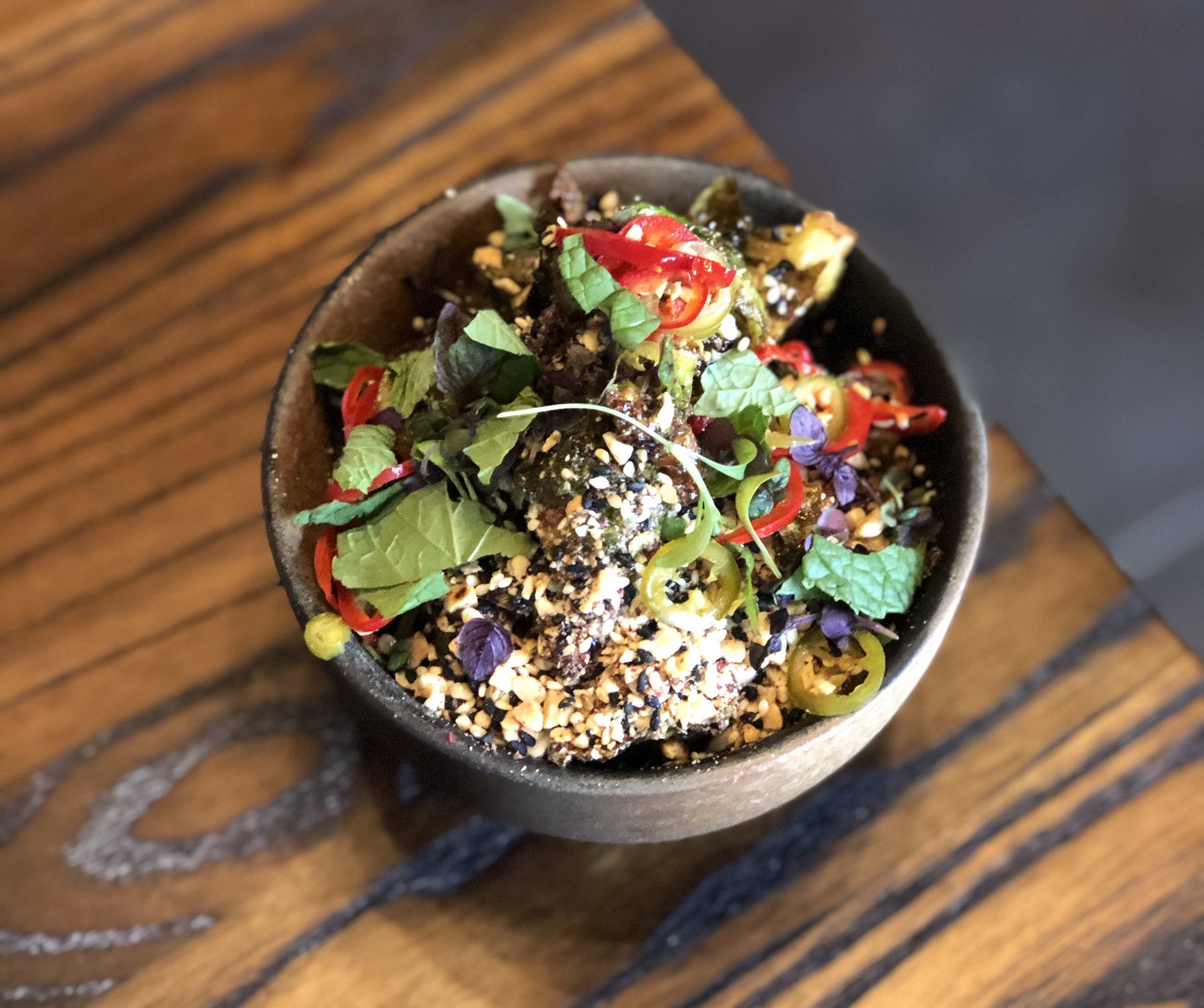 An earthenware bowl filled with fried/charred brussels sprouts garnished with sliced, red chilis, chopped herbs, black sesame seeds, and crushed peanuts
