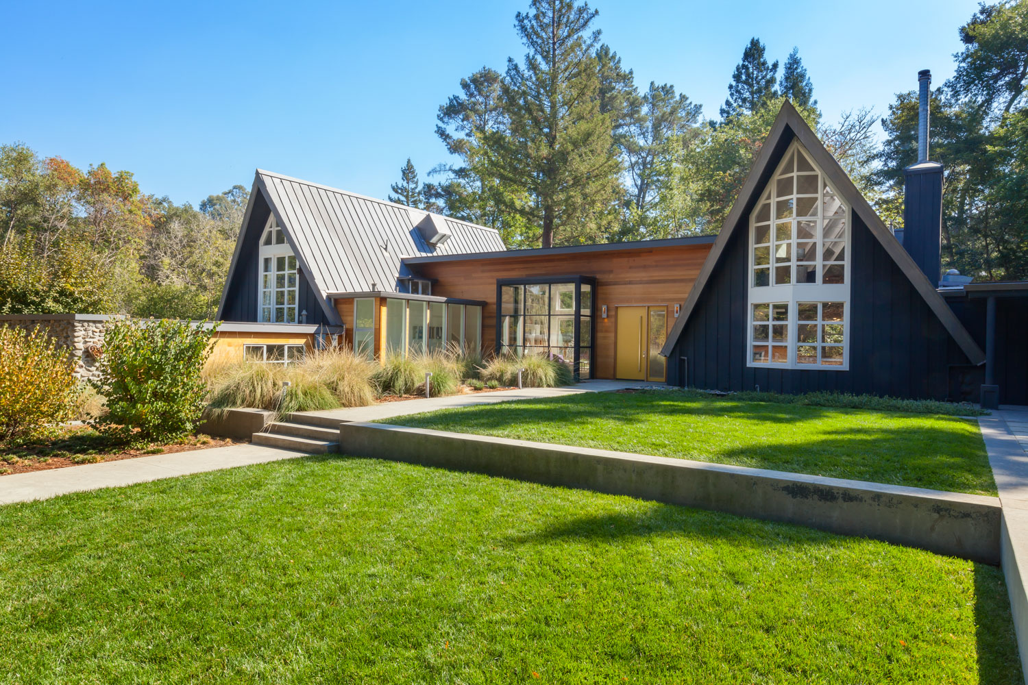 Contemporary home characterized by two A-frame structures on either end connected by flat roofed volume.