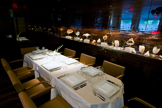 Marea's dining room has a white tablecloth and yellow chairs, set with plates and forks and knives