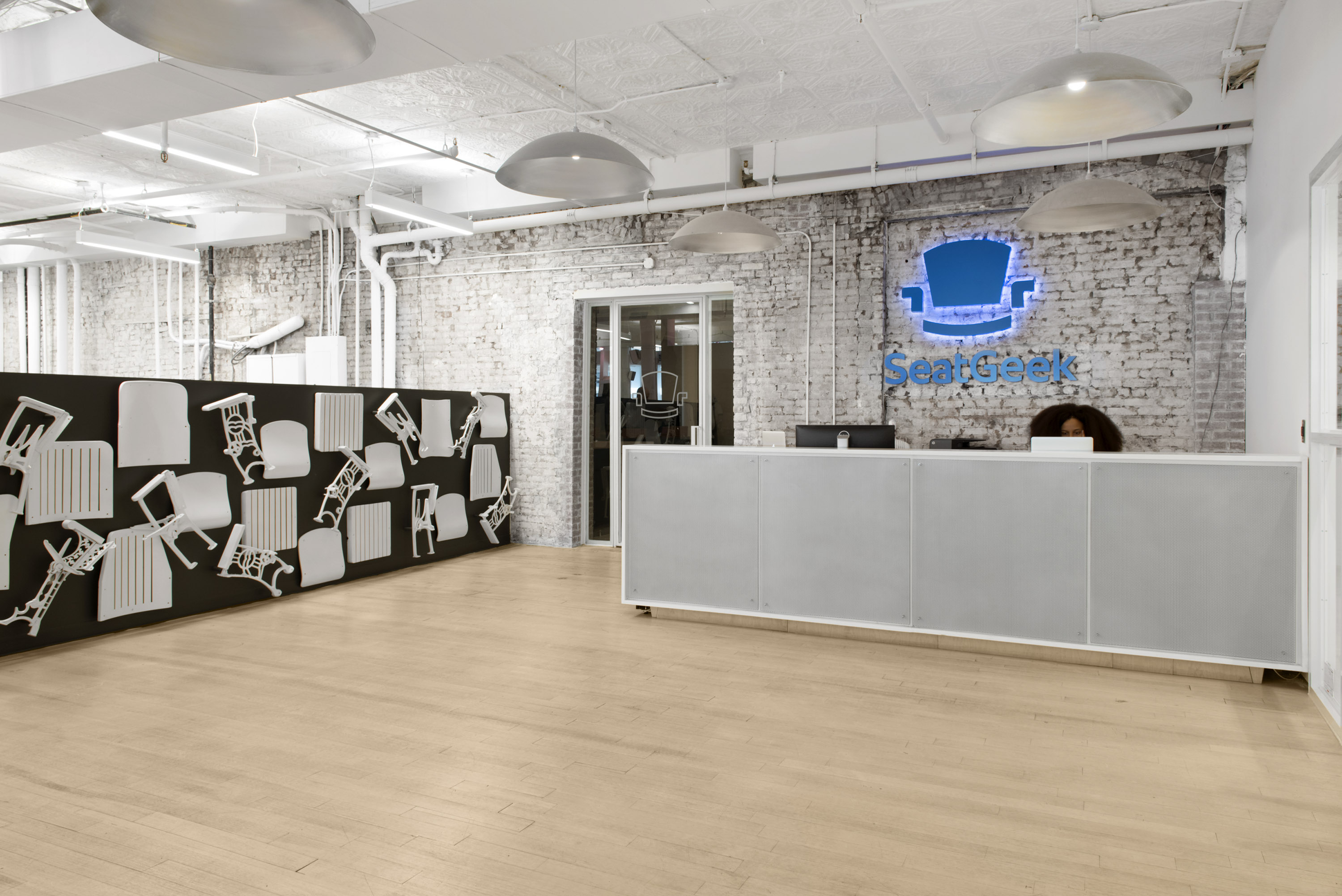 Shot of reception area of white-walled space with pale floors and a low-wall 3D mural of white-washed deconstructed stadium seats against dark blue background.