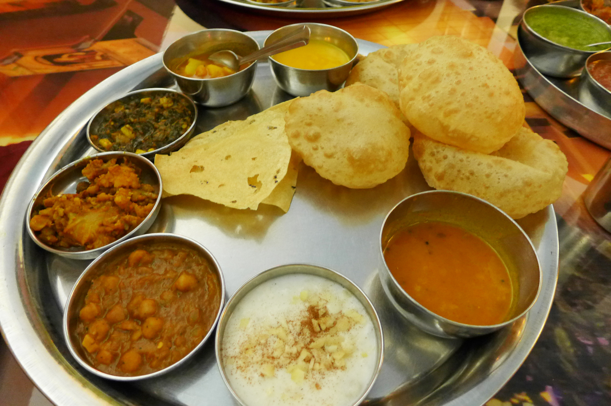 A round metal tray with little metal cups of curries and dals, with small puffy flatbreads.