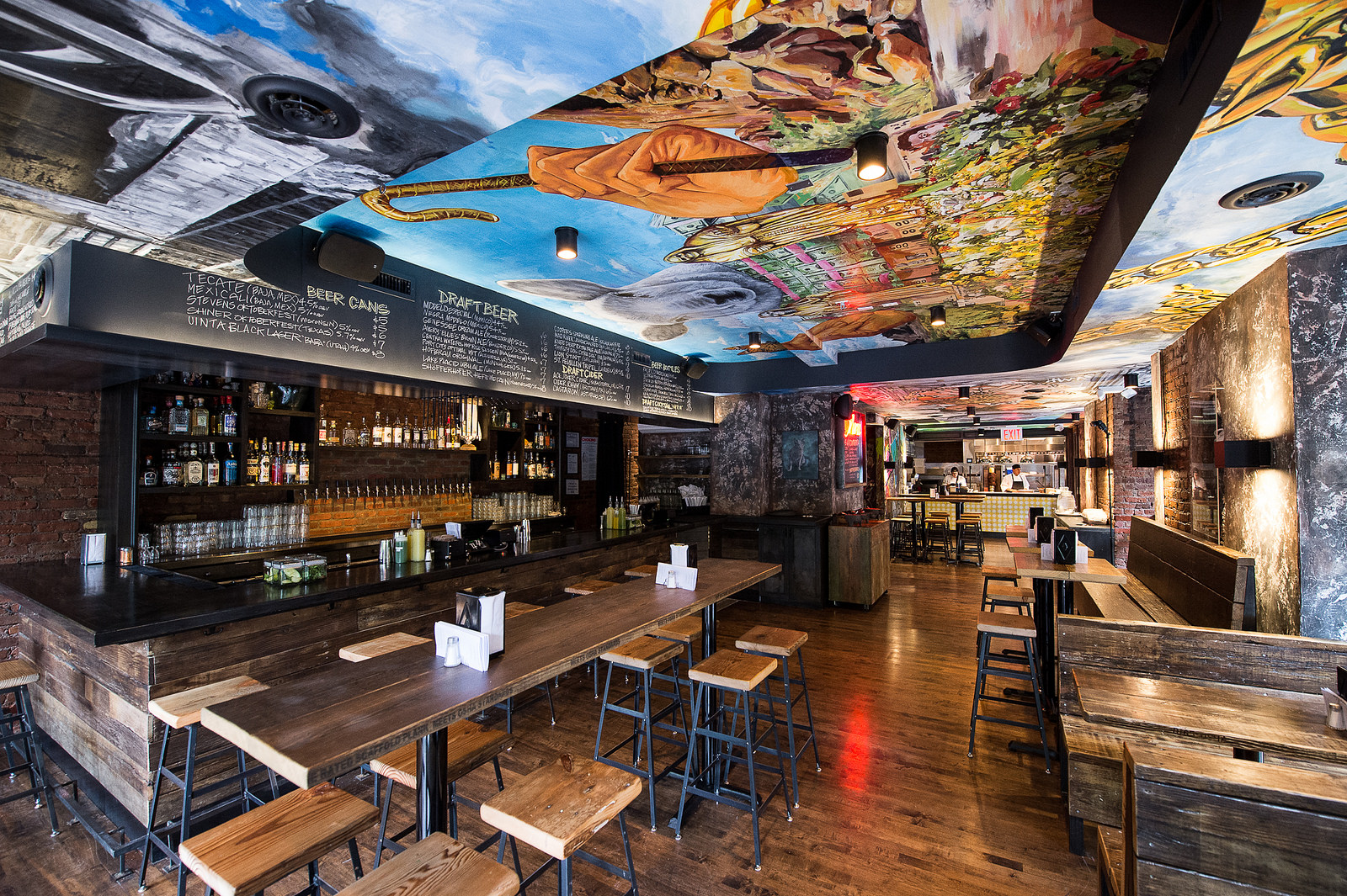 Empellon Al Pastor's dining room has wooden communal tables and a colorful painting on the ceiling.