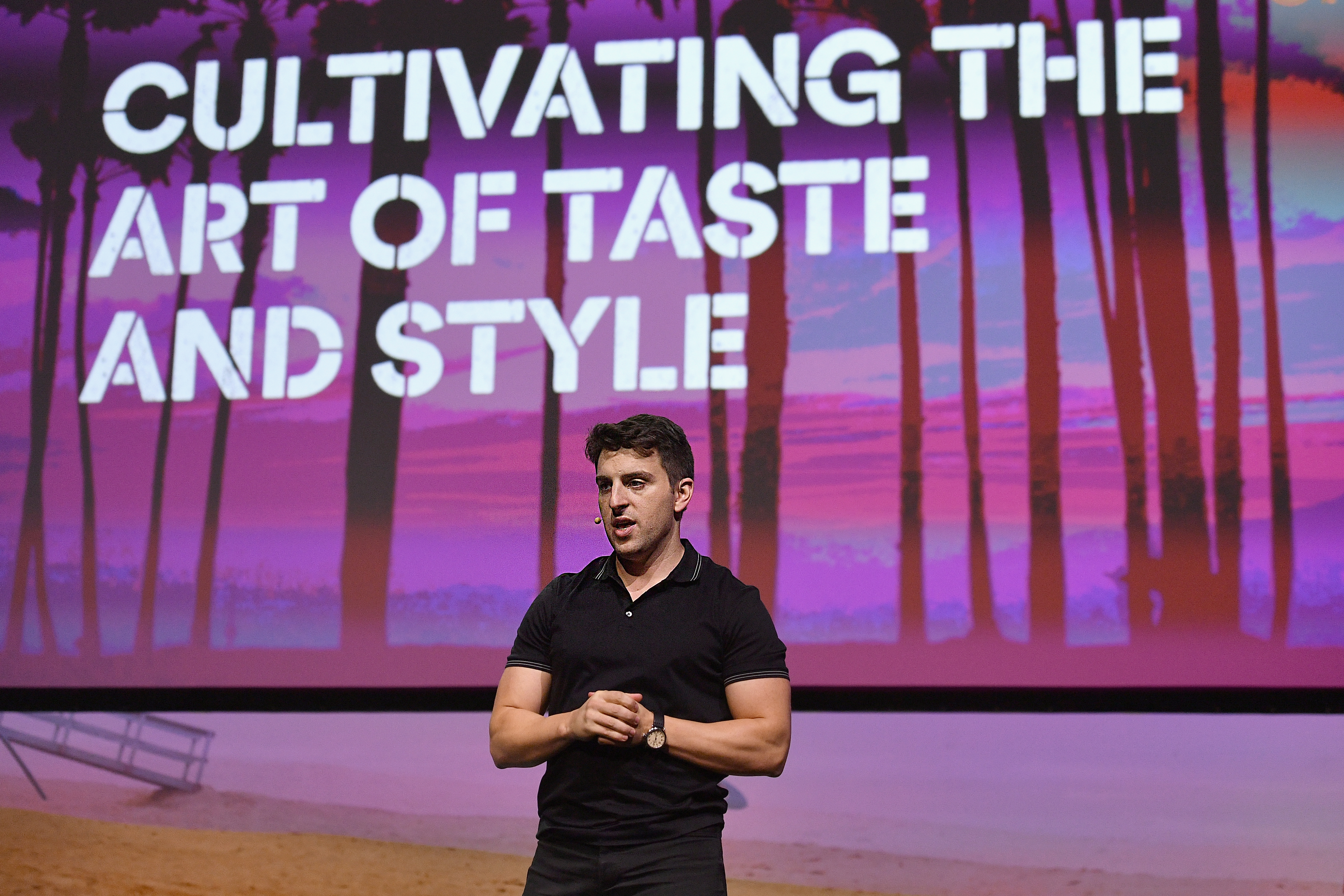 """Airbnb CEO Brian Chesky onstage in front of a sign reading, """"Cultivating the art of taste and style."""""""