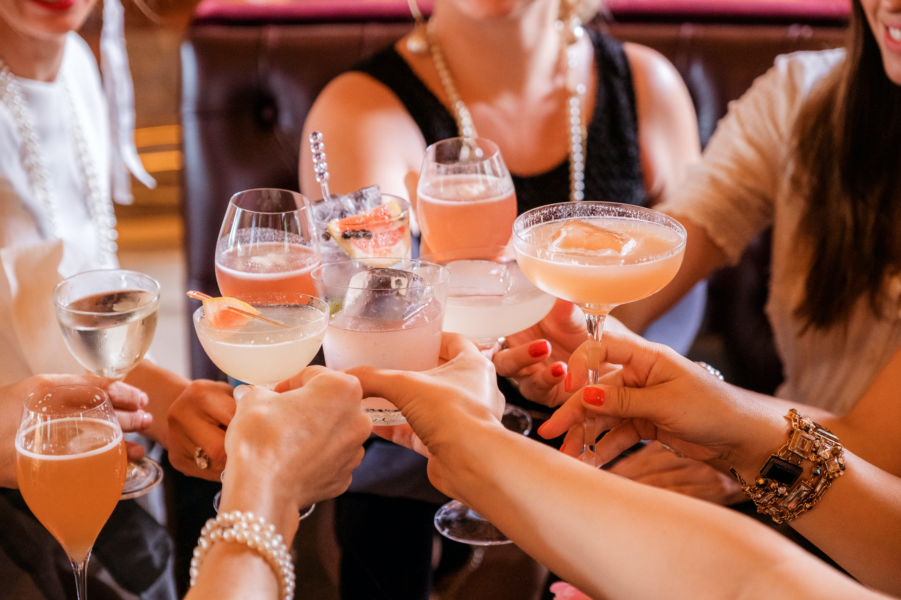 group of people with cocktails in their hands cheering