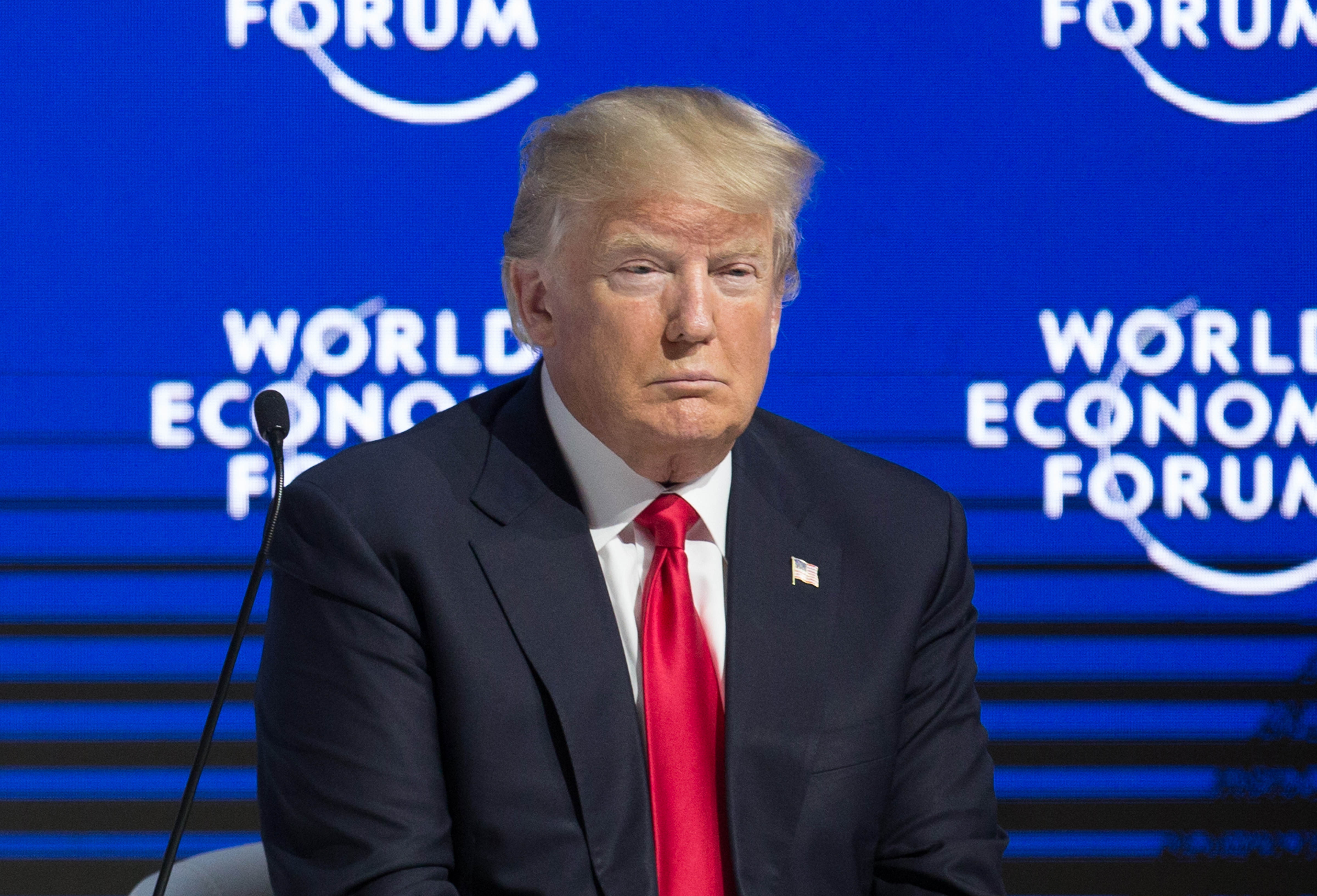 President Donald Trump sits in front of a blue wall that reads World Economic Forum in Davos, Switzerland.