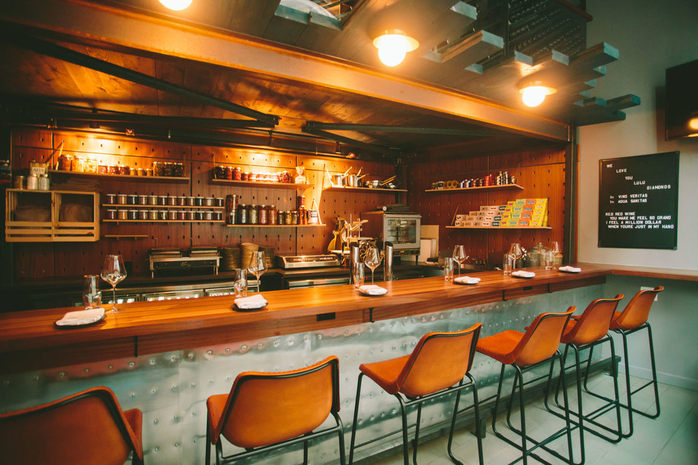 The interior of an intimate wine bar that has a bit of a nautical vibe