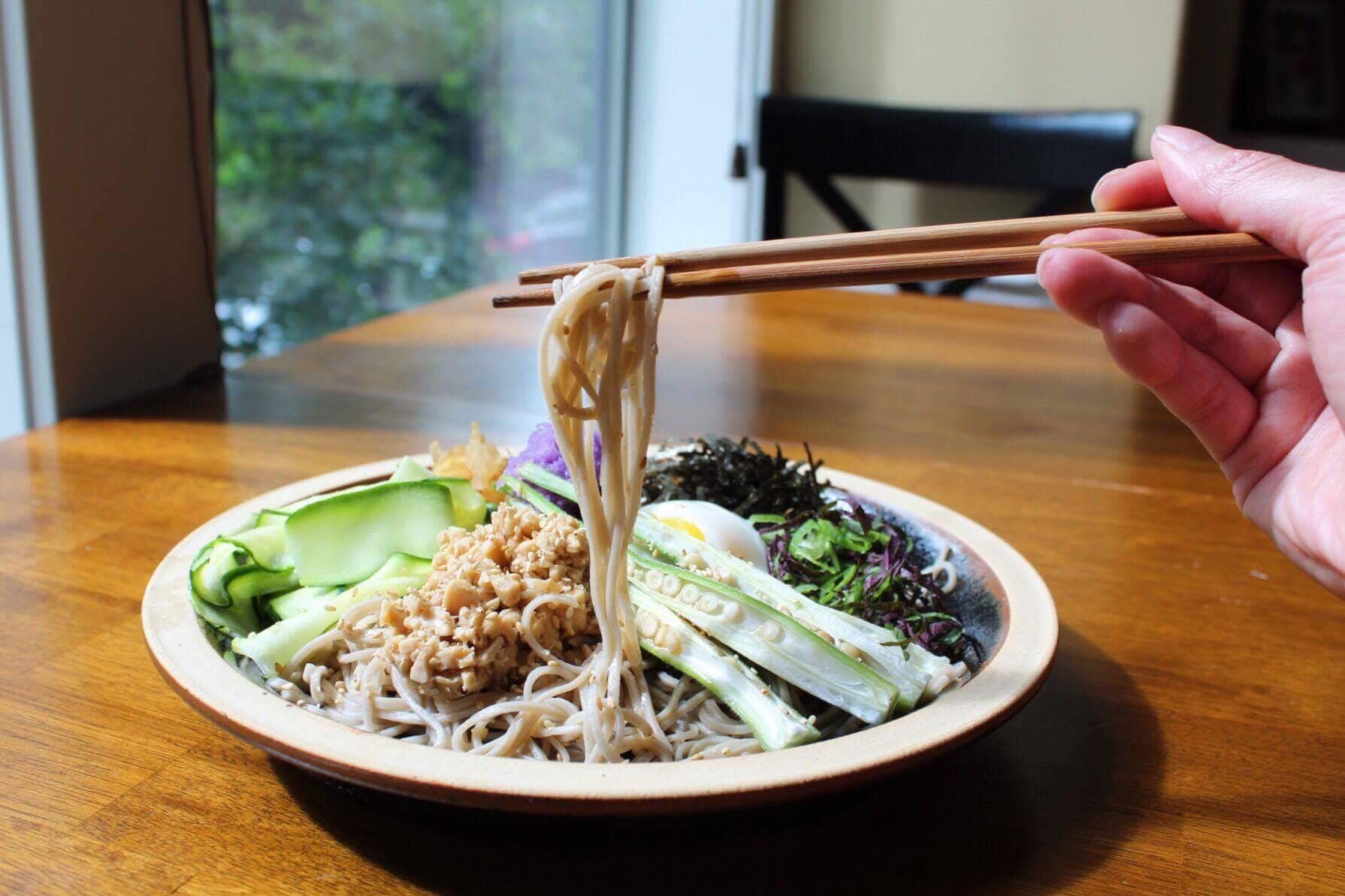 Chopsticks pulling buckwheat soba noodles from a plate of green vegetables.