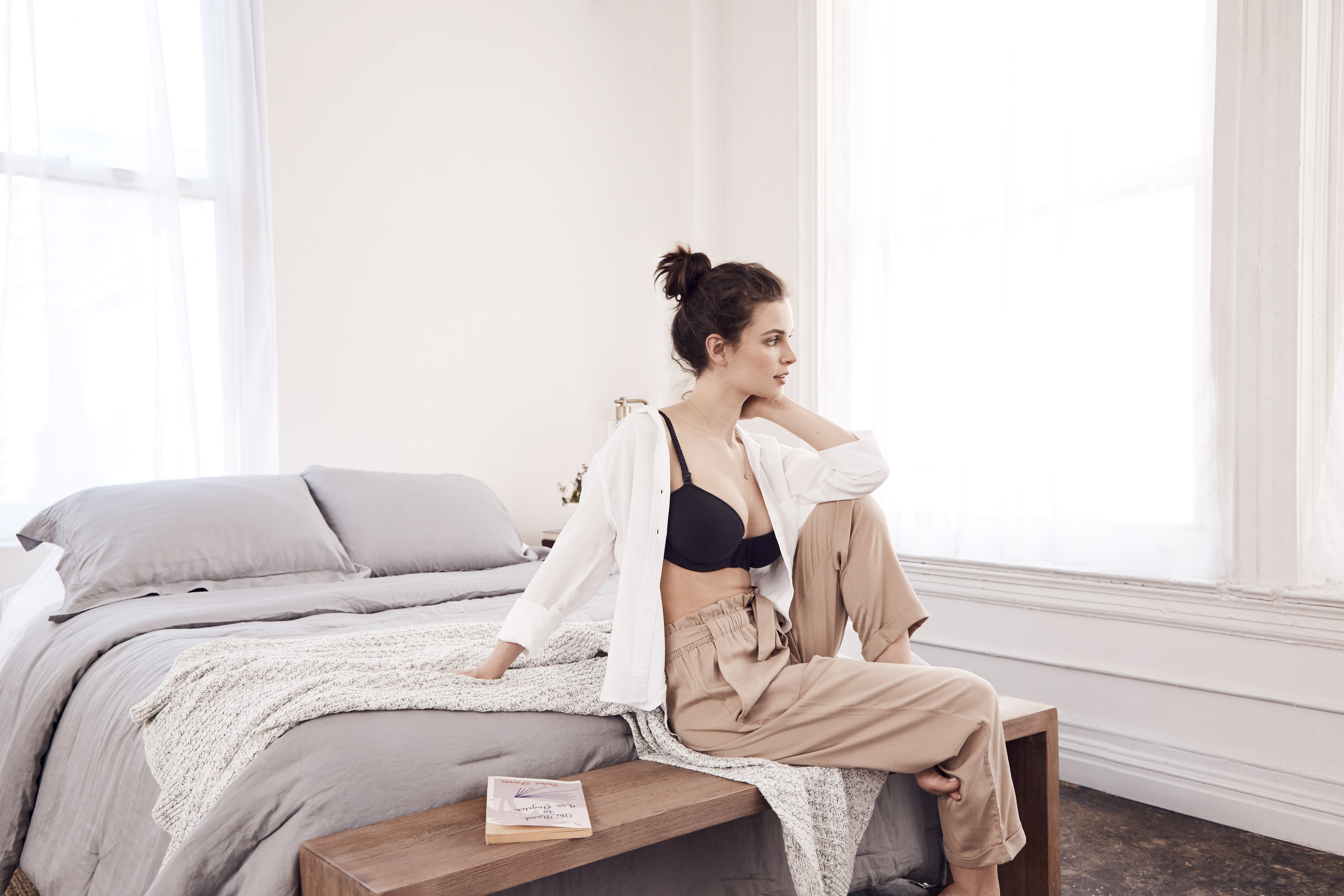 A woman sits on a bed in a black bra and khaki pants