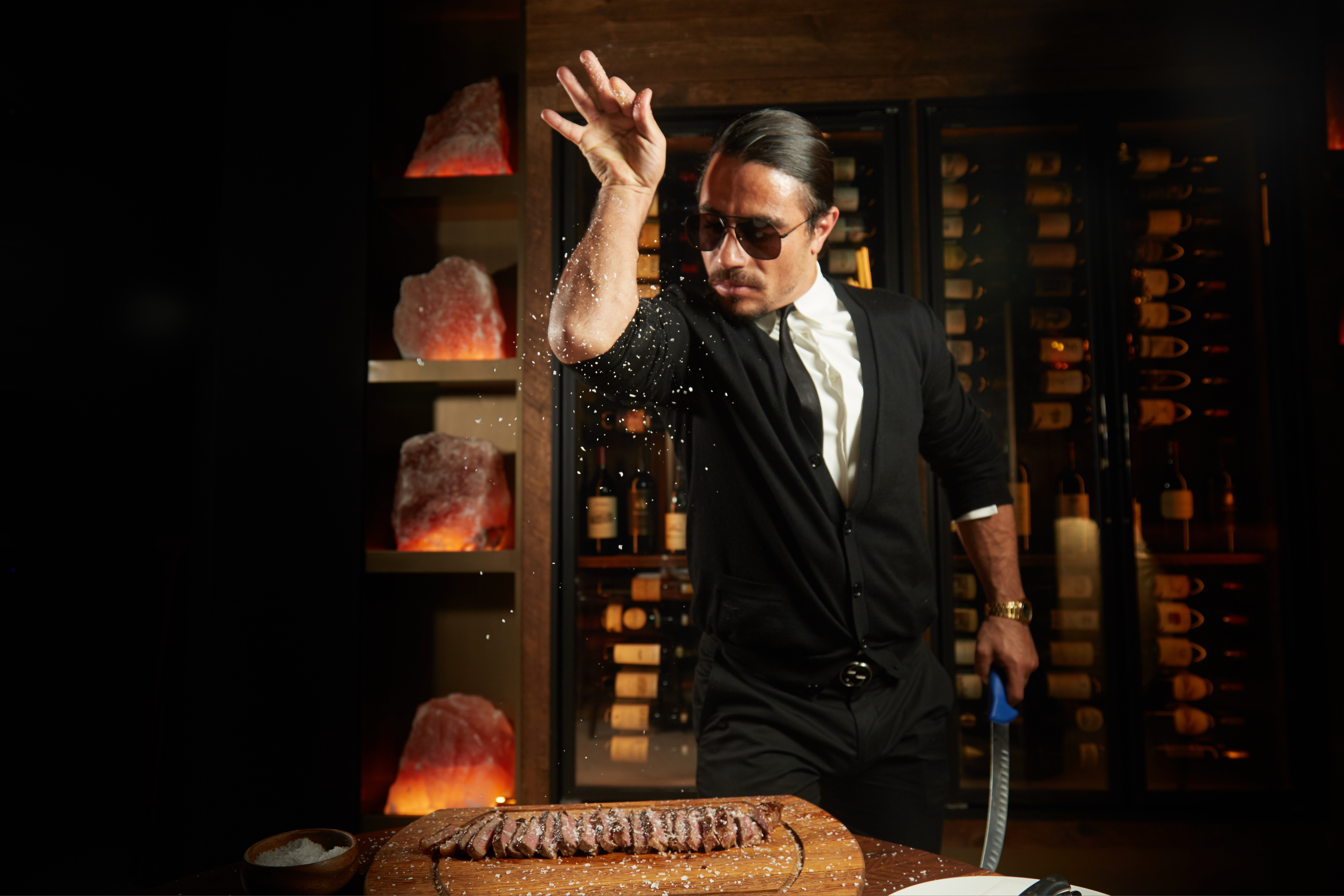 A man in dark sunglasses in a signature salt-sprinkling post stands over a cutting board with sliced steak.