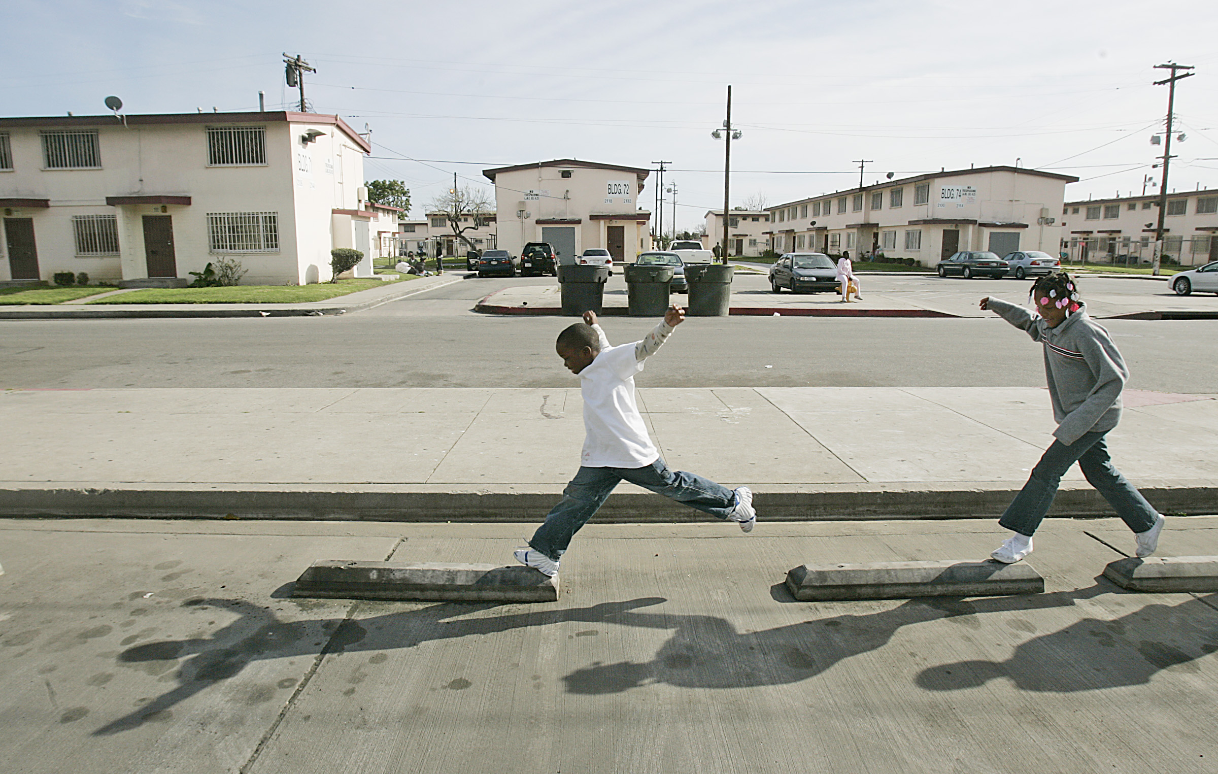 Tyrell Coleman, 7, and his sister Ranisha, 10, play in a parking lot at the Jordan Downs housing pr