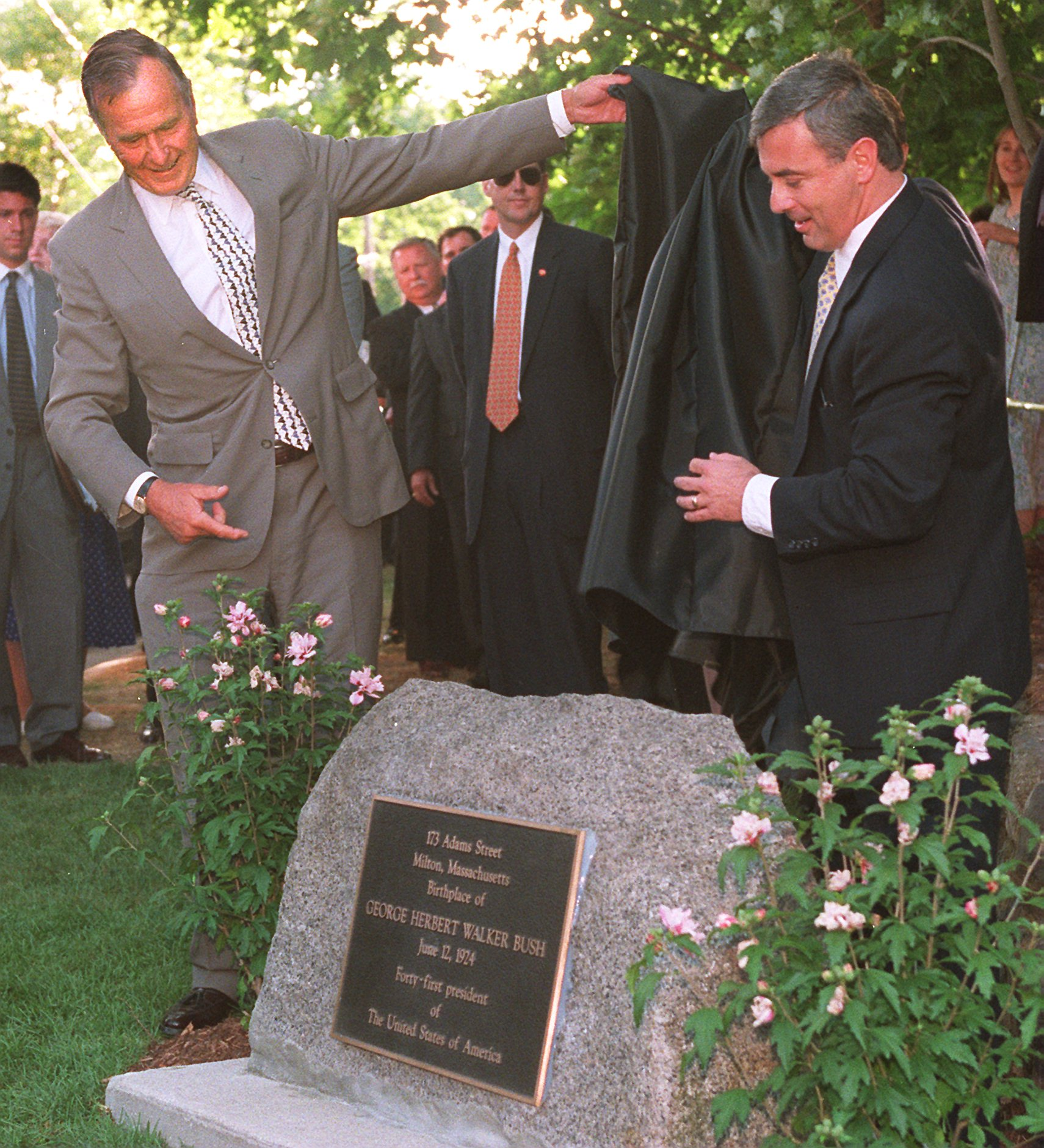 Two men taking a cover off a stone with a plaque on it, and there's a crowd behind them.