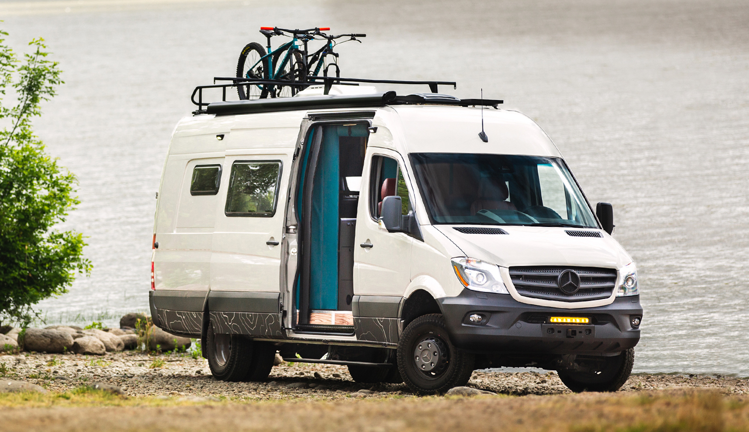 A white camper van sits on the banks of a lake. The camper van's side door is open and there is a roof rack with two bikes on top.