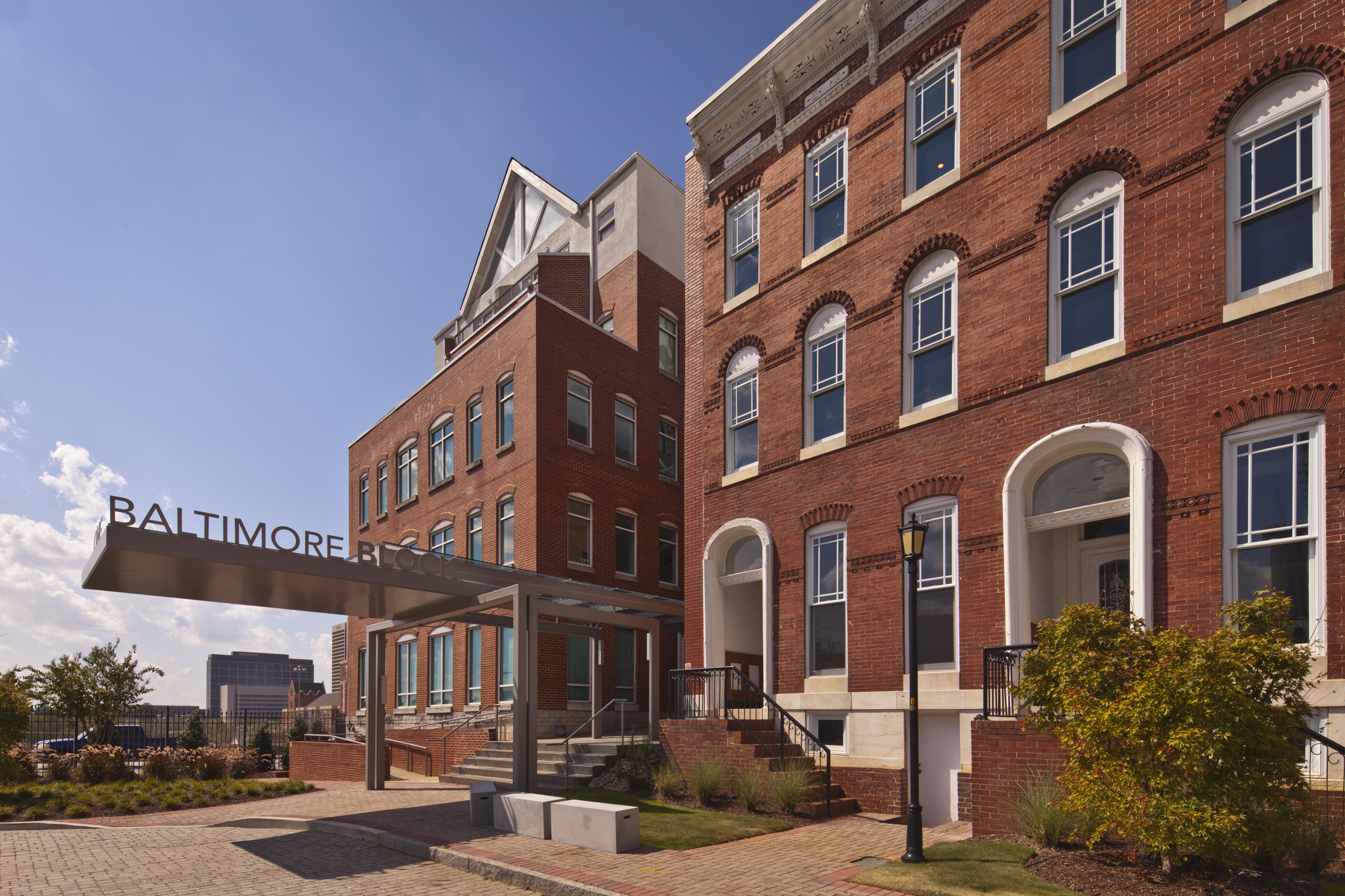 A brick building with modern metal entry, abutting the 1880s row houses.