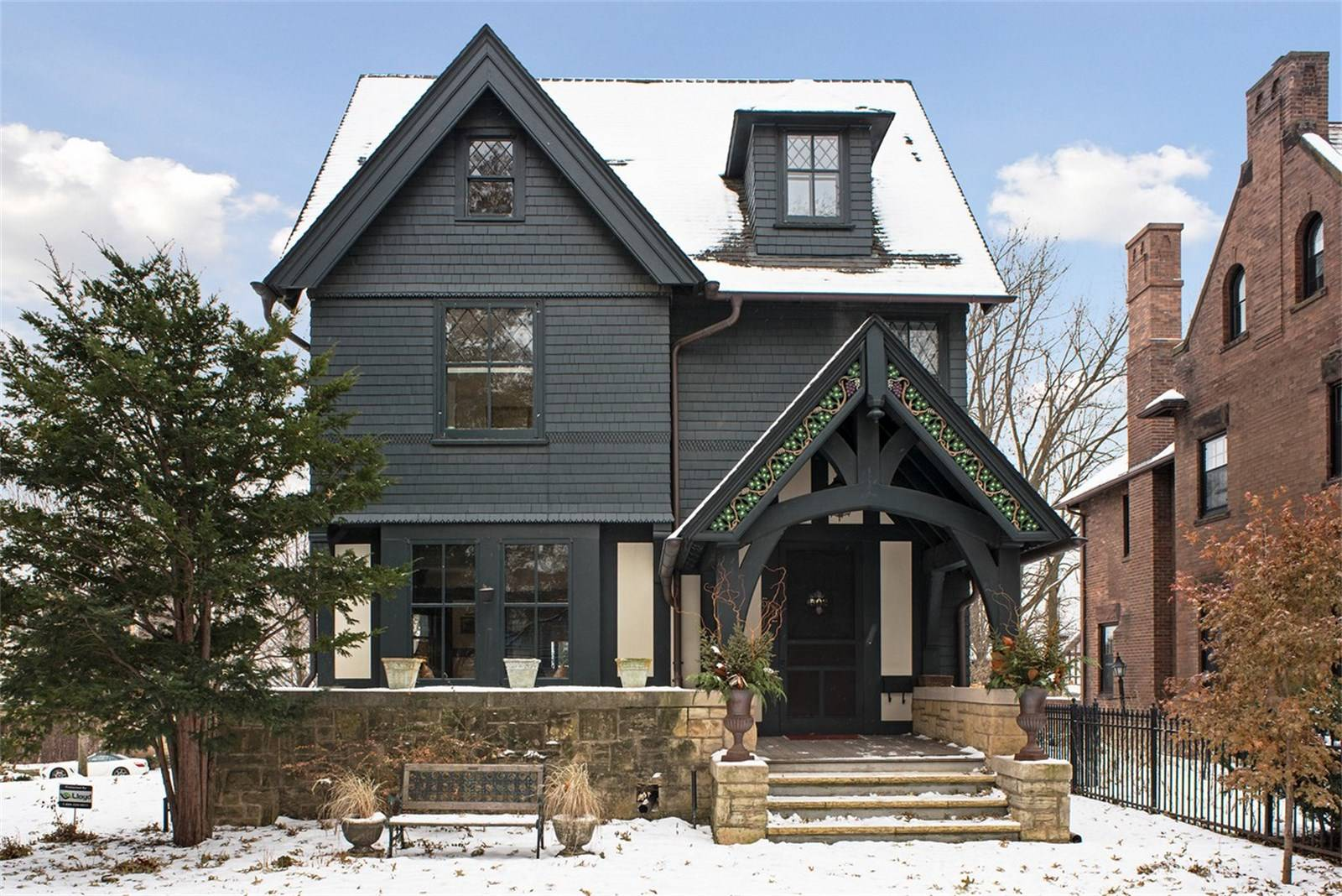 Dark blue-painted wood-frame house with covered stone porch dusted with snow.