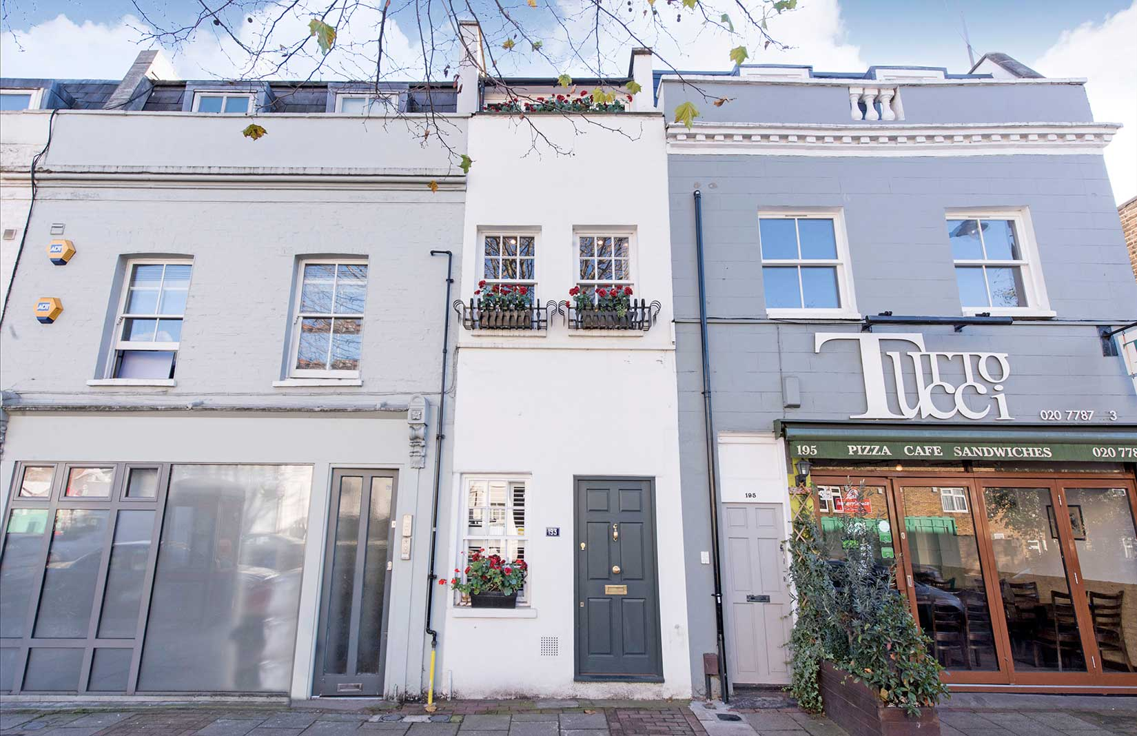 Shot of very narrow home with white facade and windows with planters wedged between two wider buildings.