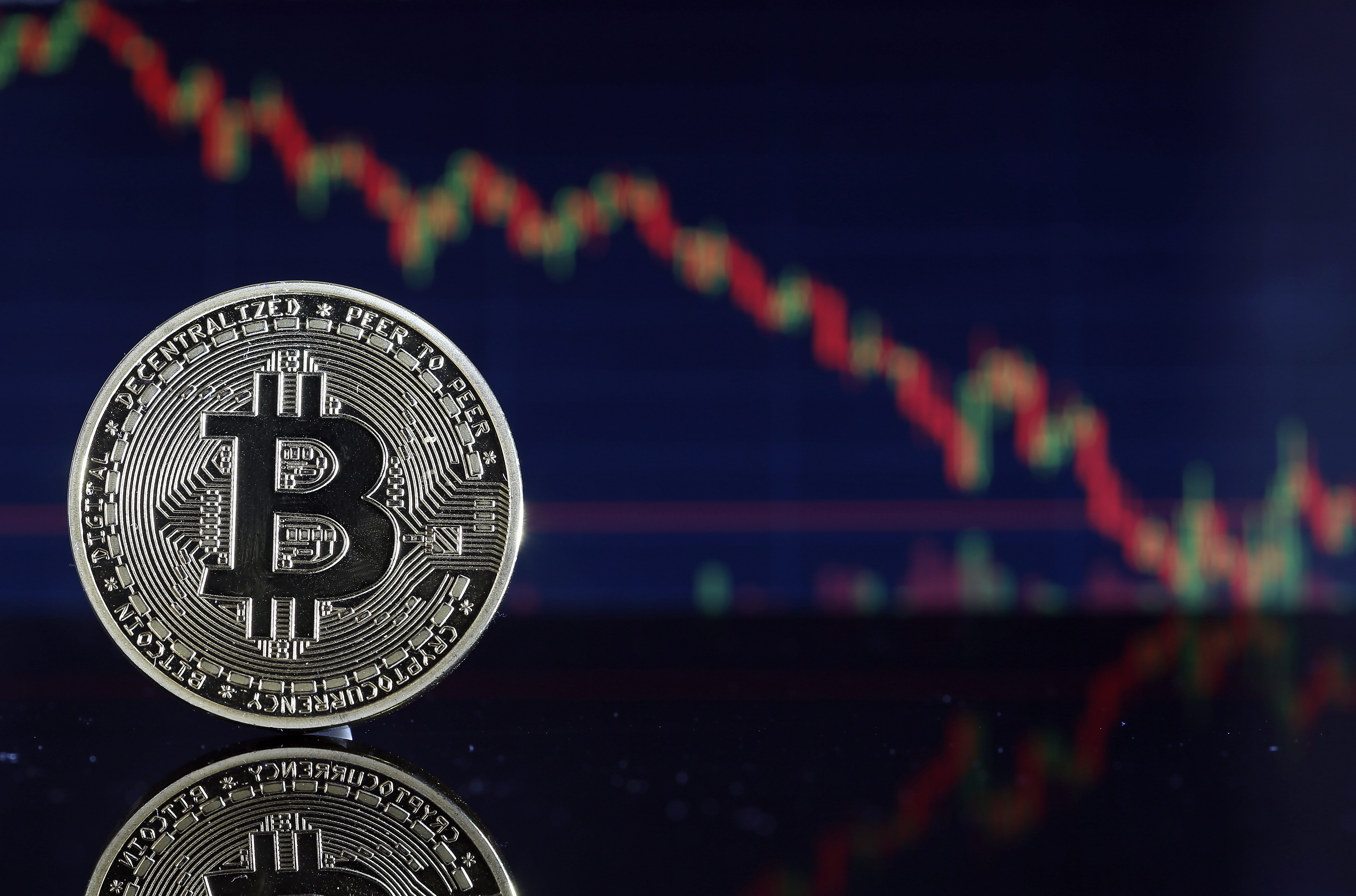 """An illustration of a bitcoin """"coin"""" with a falling stock chart in the background"""