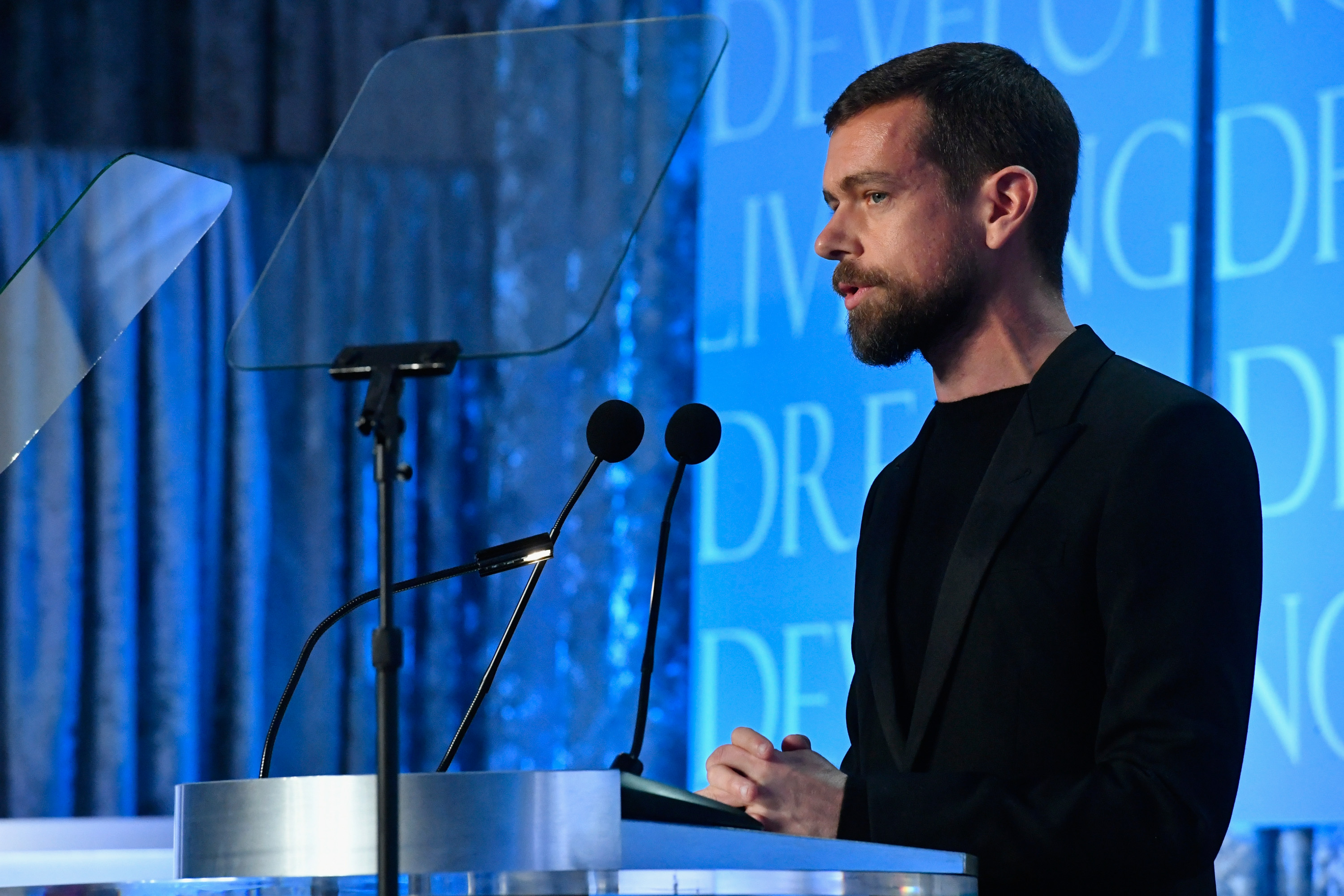 Twitter CEO Jack Dorsey onstage speaking from a podium into a pair of microphones