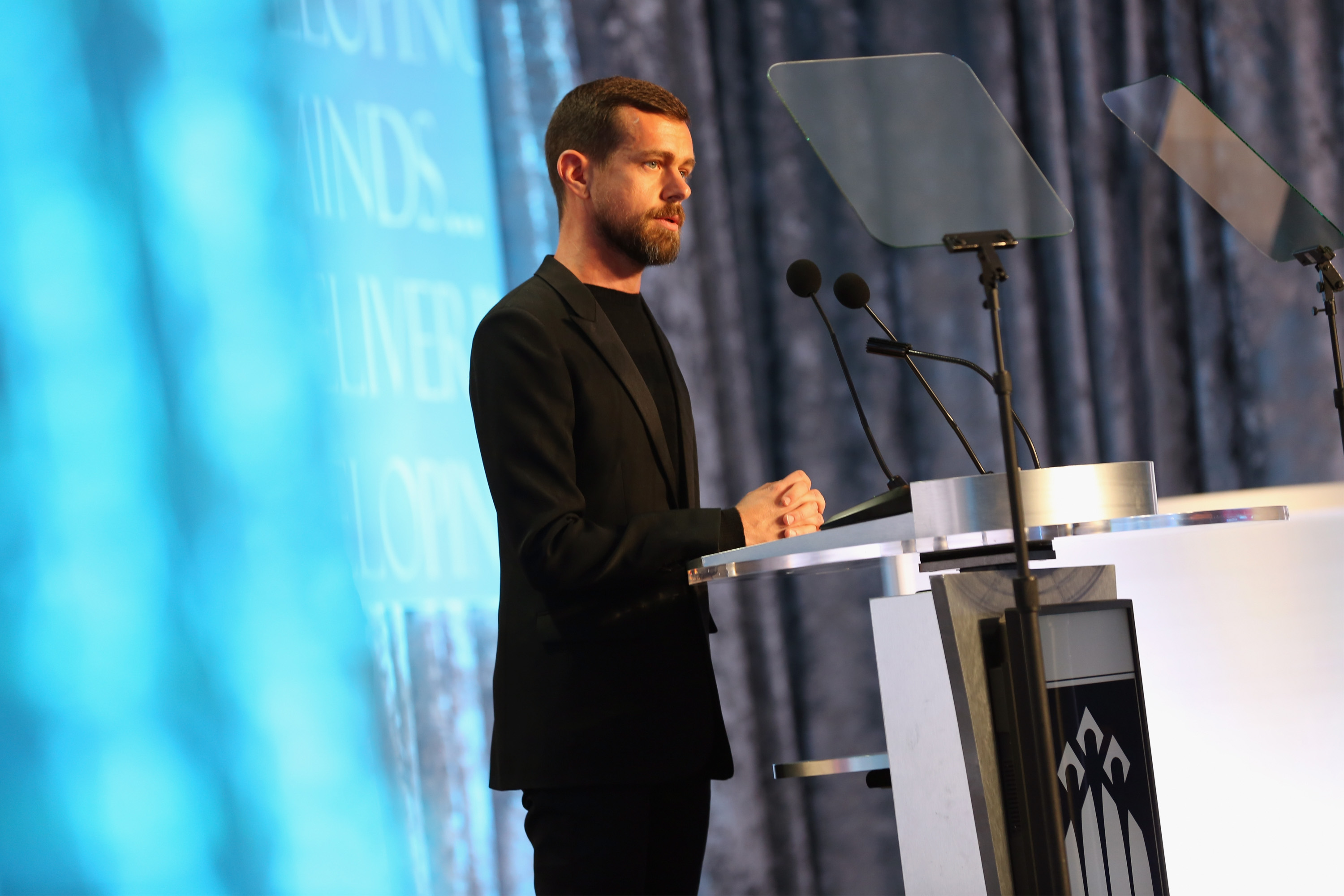 Twitter CEO Jack Dorsey stands at a podium and speaks into microphones