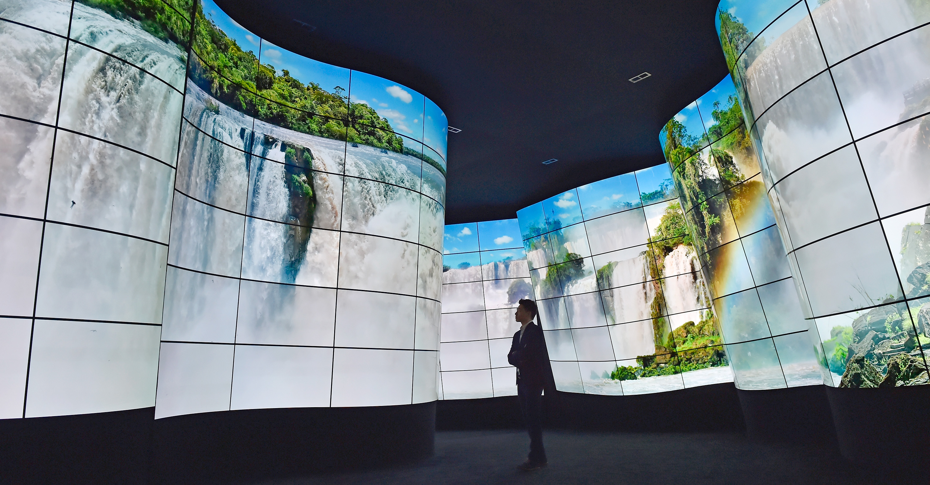 A person stands looking at walls that are a giant curved screen showing a waterfall landscape.