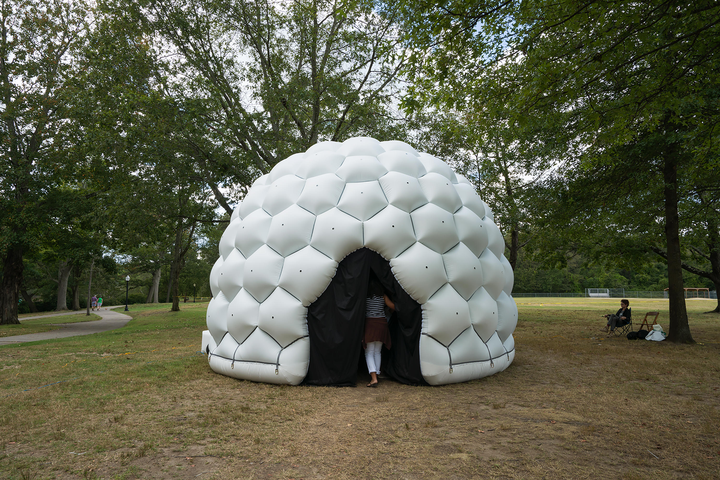 White inflatable dome structure with in a park.