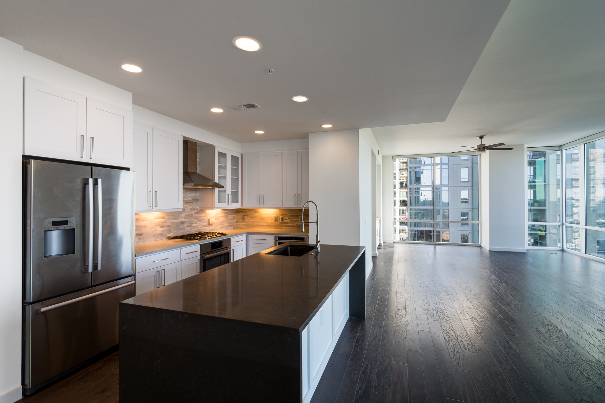 A large kitchen with dark quartz countertops, opening to a large glassy room with dark wood floors.