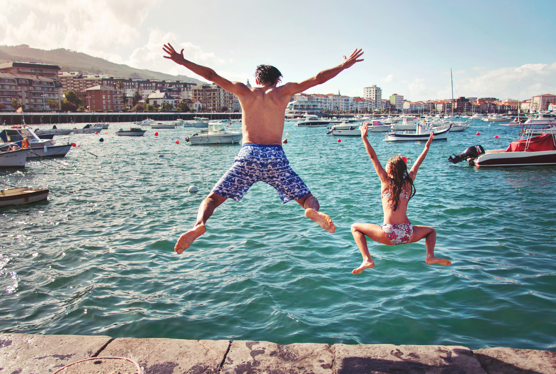 A man and a child jumping off a dock into the ocean.
