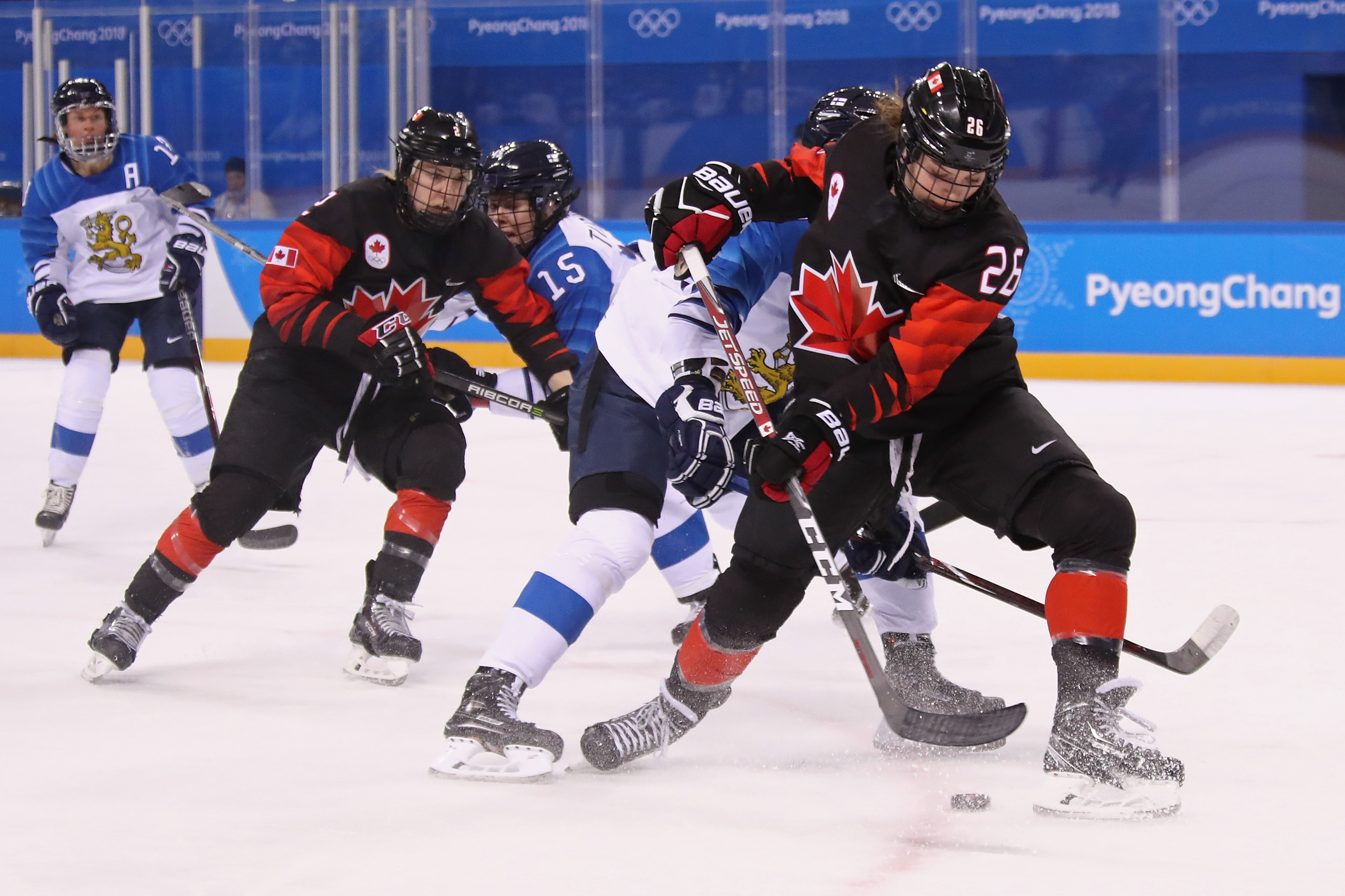 Emily Clark #26 of Canada battles for the puck against Finland in the second period during the Women's Ice Hockey Preliminary Round
