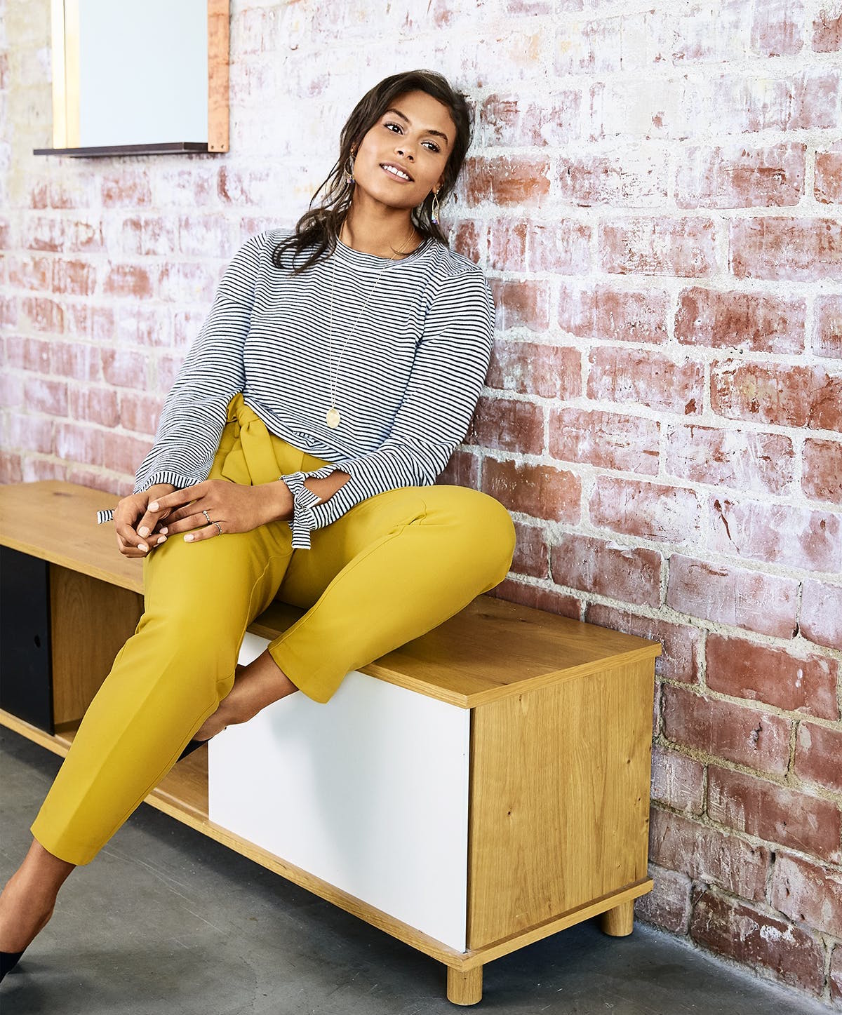 A model in yellow pants and a striped top leaning against a brick wall