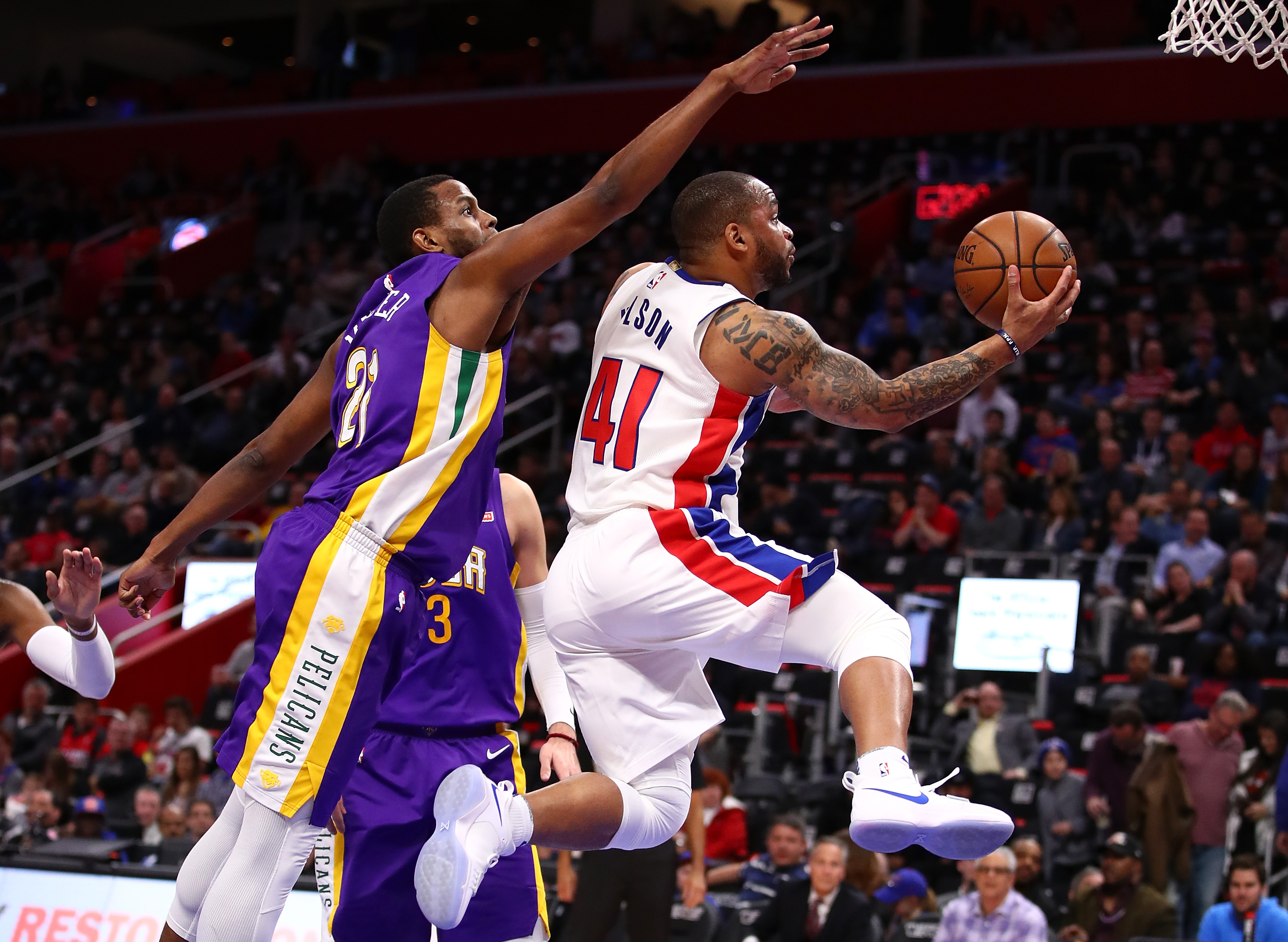 A Detroit Pistons basketball player goes up for a basket while a New Orleans player jumps behind him