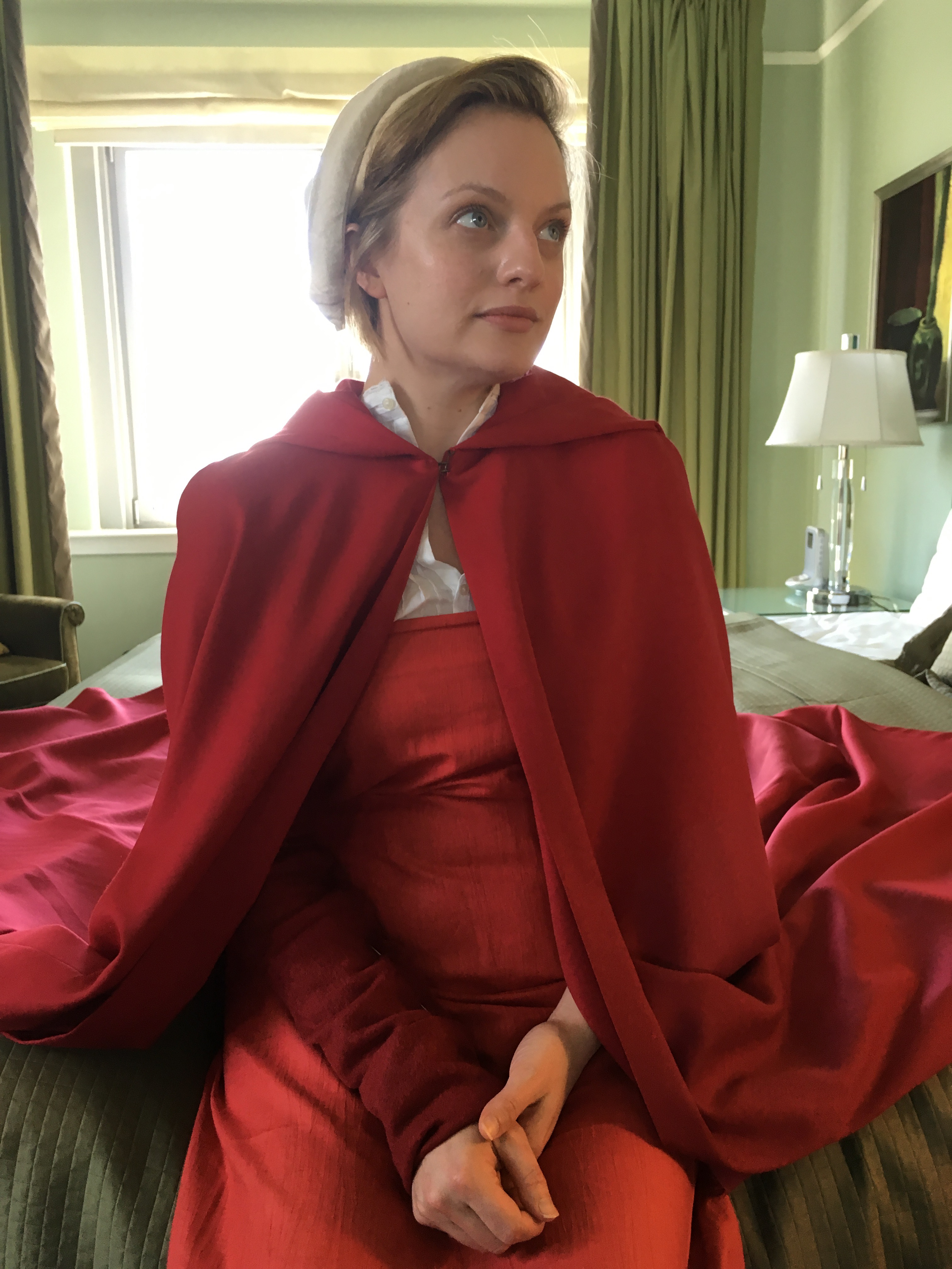 """Actress Elizabeth Moss wears the red dress and white hat from """"The Handmaid's Tale"""" TV show."""