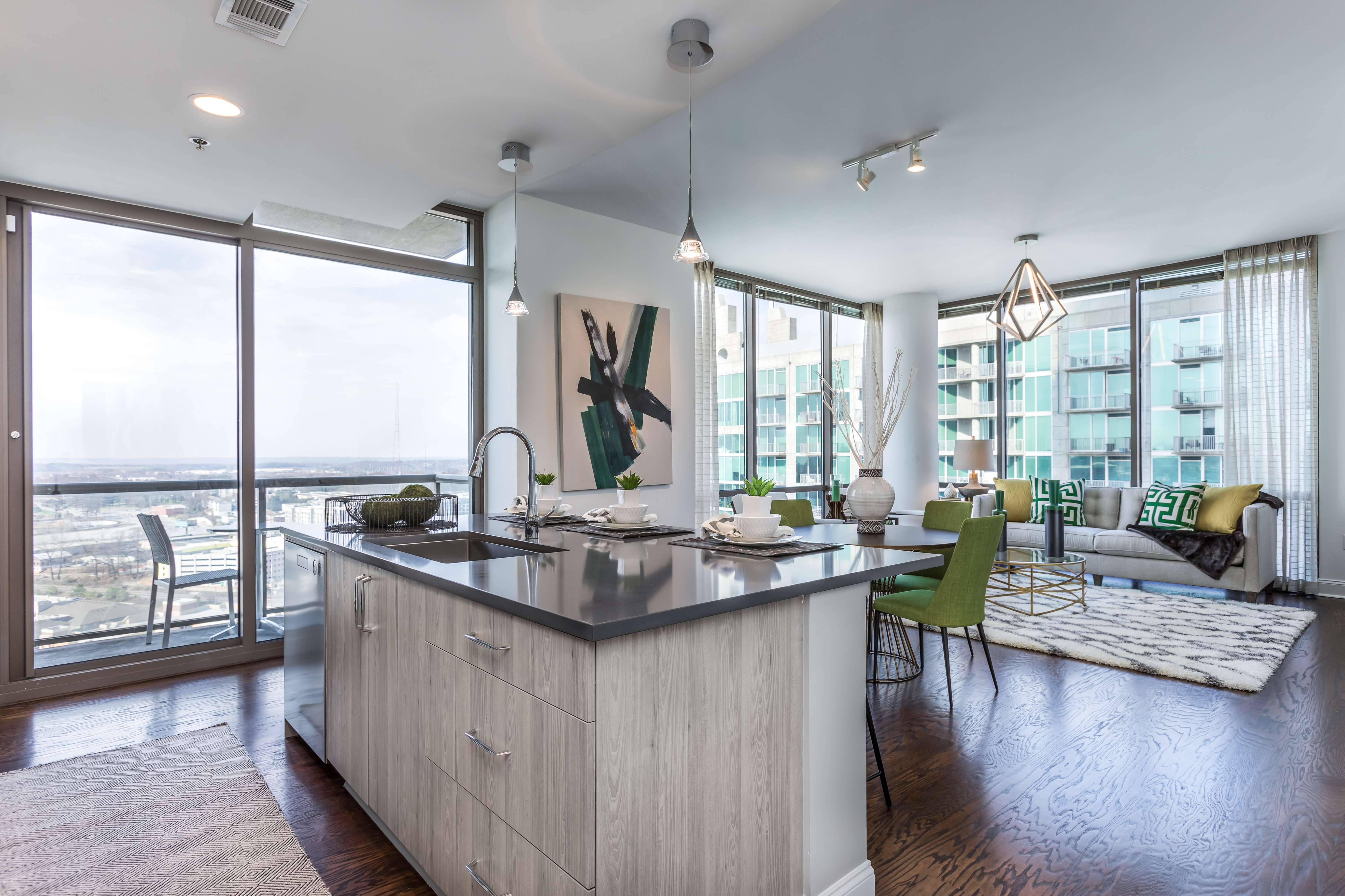 A bright kitchen with hardwood floors, facing an open living space with large windows.
