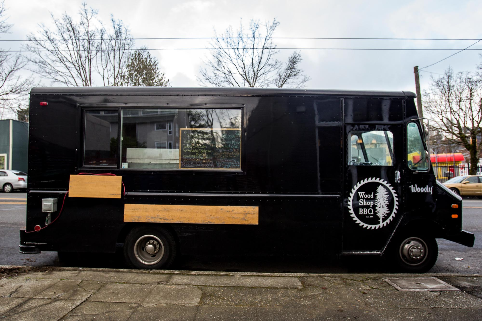 The side view of a black food truck with the Wood Shop BBQ logo in white on the door.