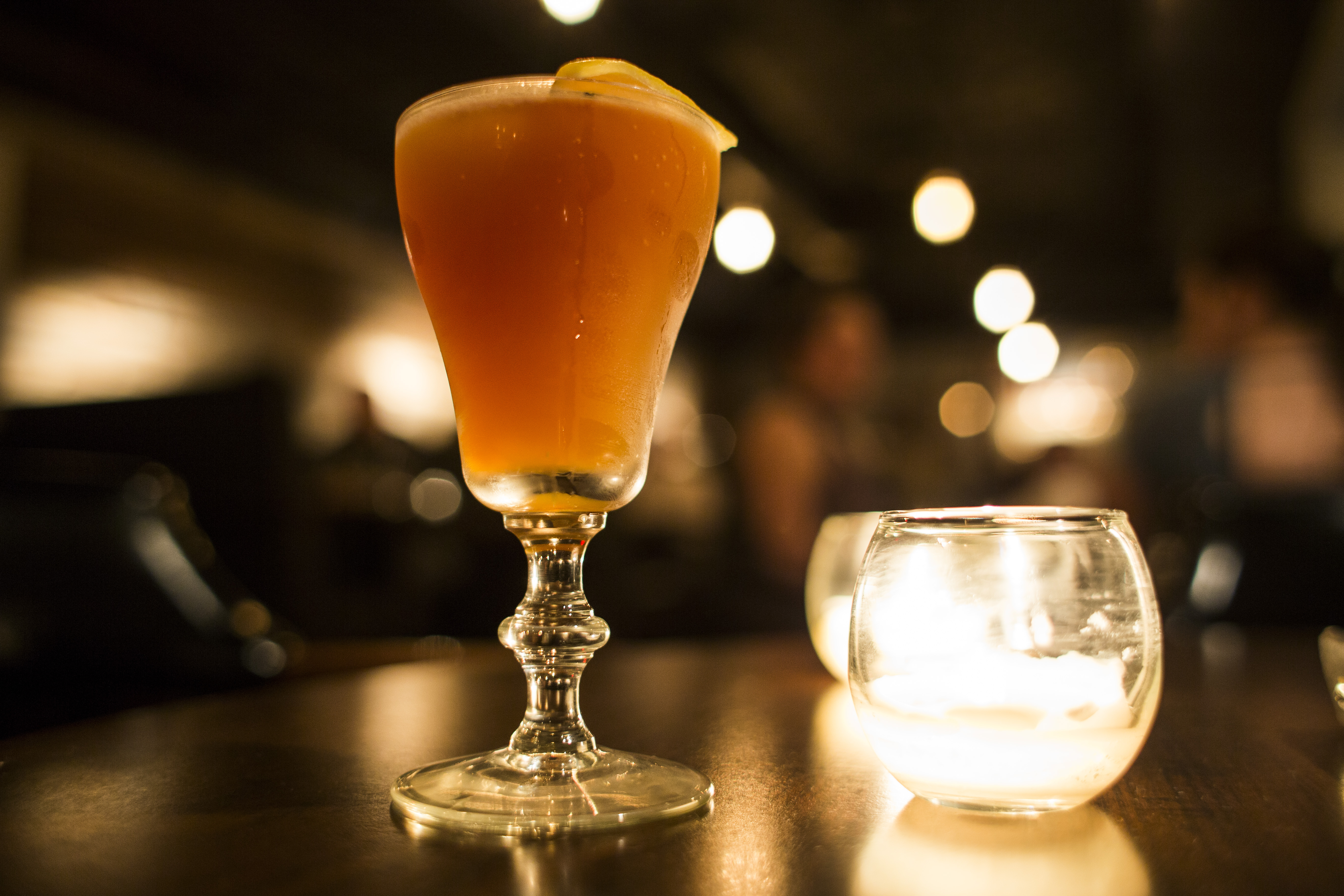 The orange colored cocktail sits next to a glass candle holder on a wooden table in a dimly lit bar.