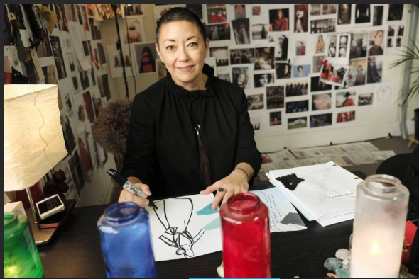 Costume designer Ane Crabtree sitting at her desk surrounded by pictures