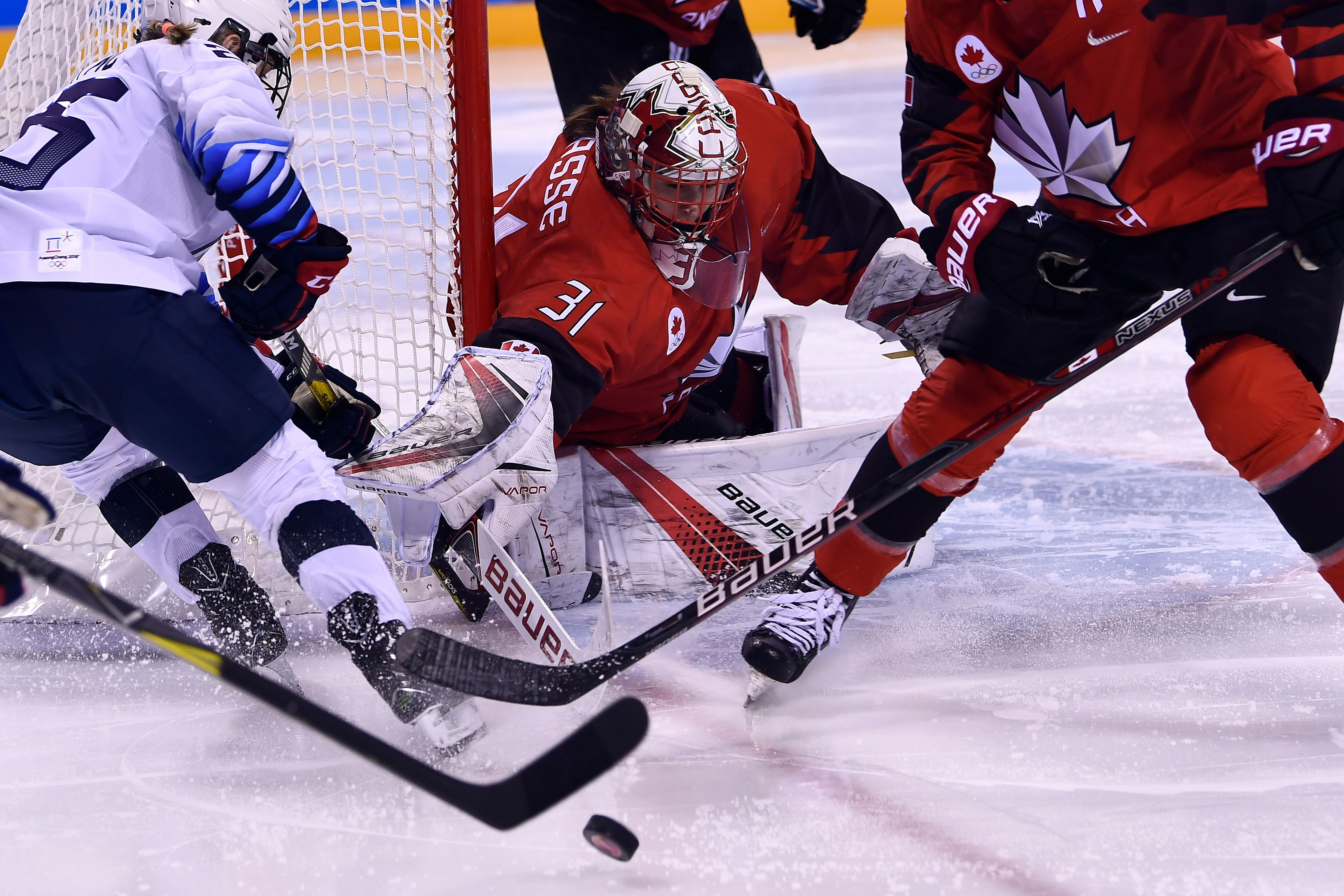 Canada's Genevieve Lacasse (C) defends her goal in the women's preliminary round ice hockey match between the US and Canada