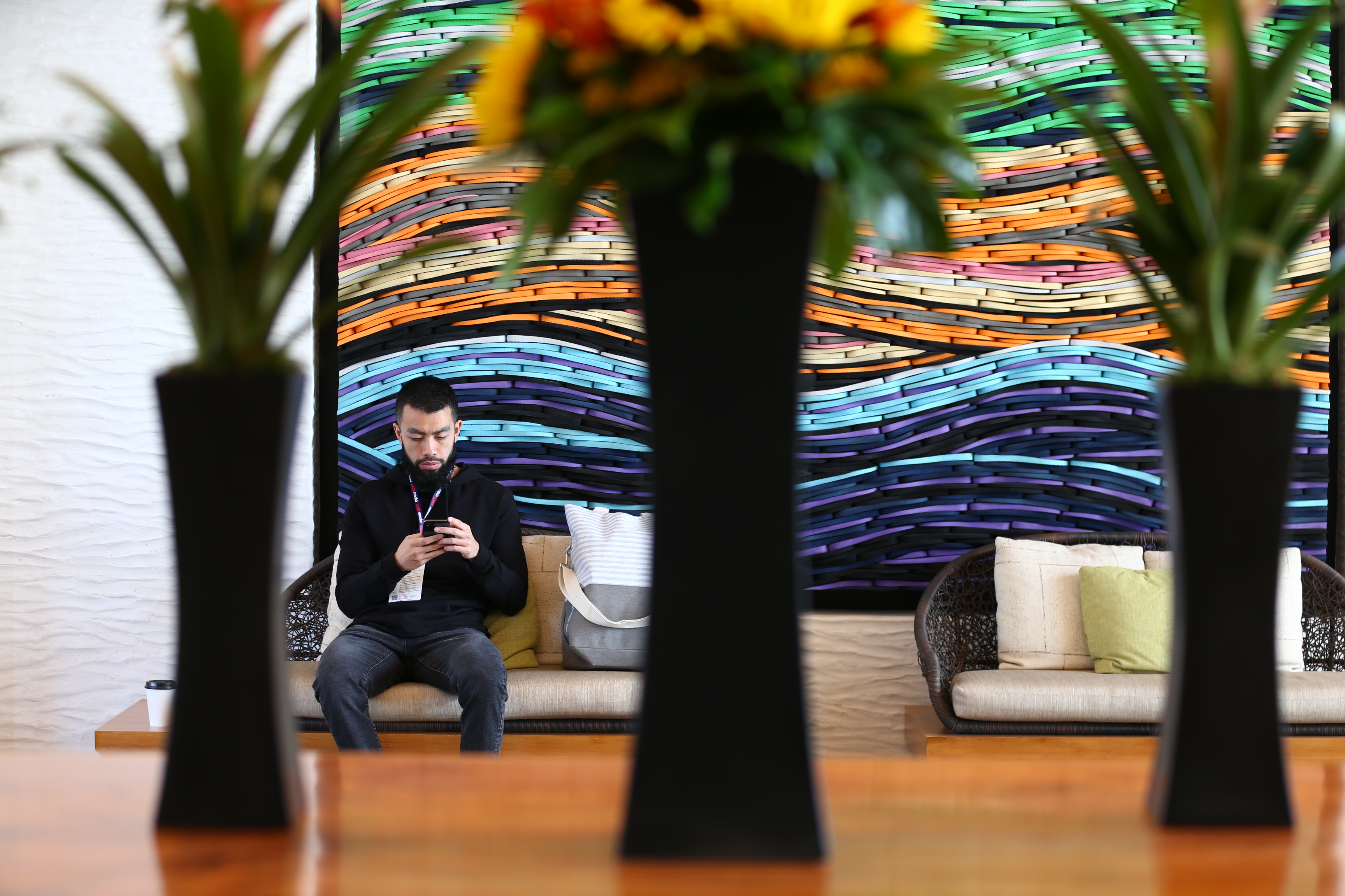 A man sits in a hotel lobby looking at his phone.