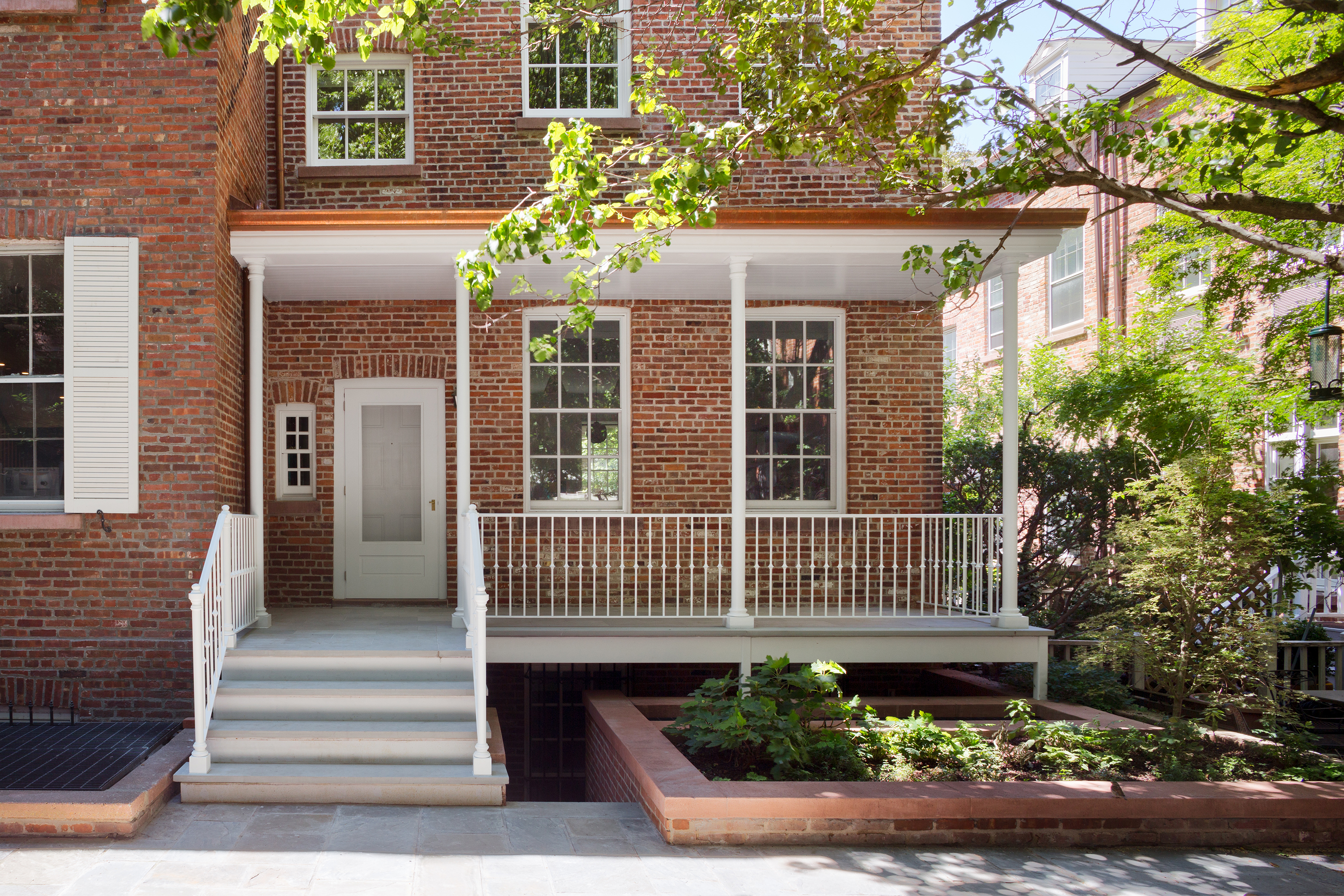 The exterior of a townhouse. The facade is red brick. There are white stairs and a white porch. The door is painted white. There are multiple windows and a garden.