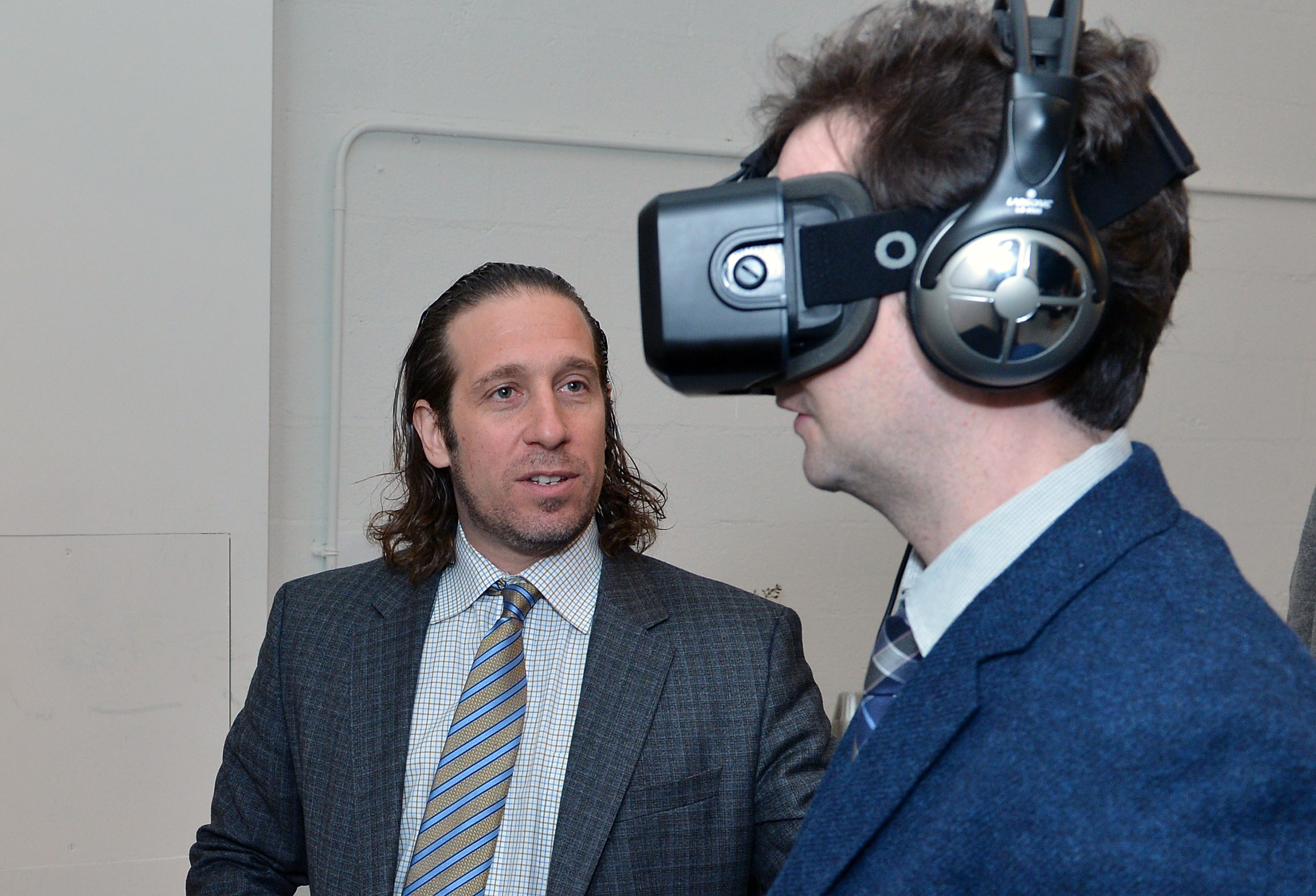 Stanford Professor Jeremy Bailenson (left) coaches a person wearing a VR headset