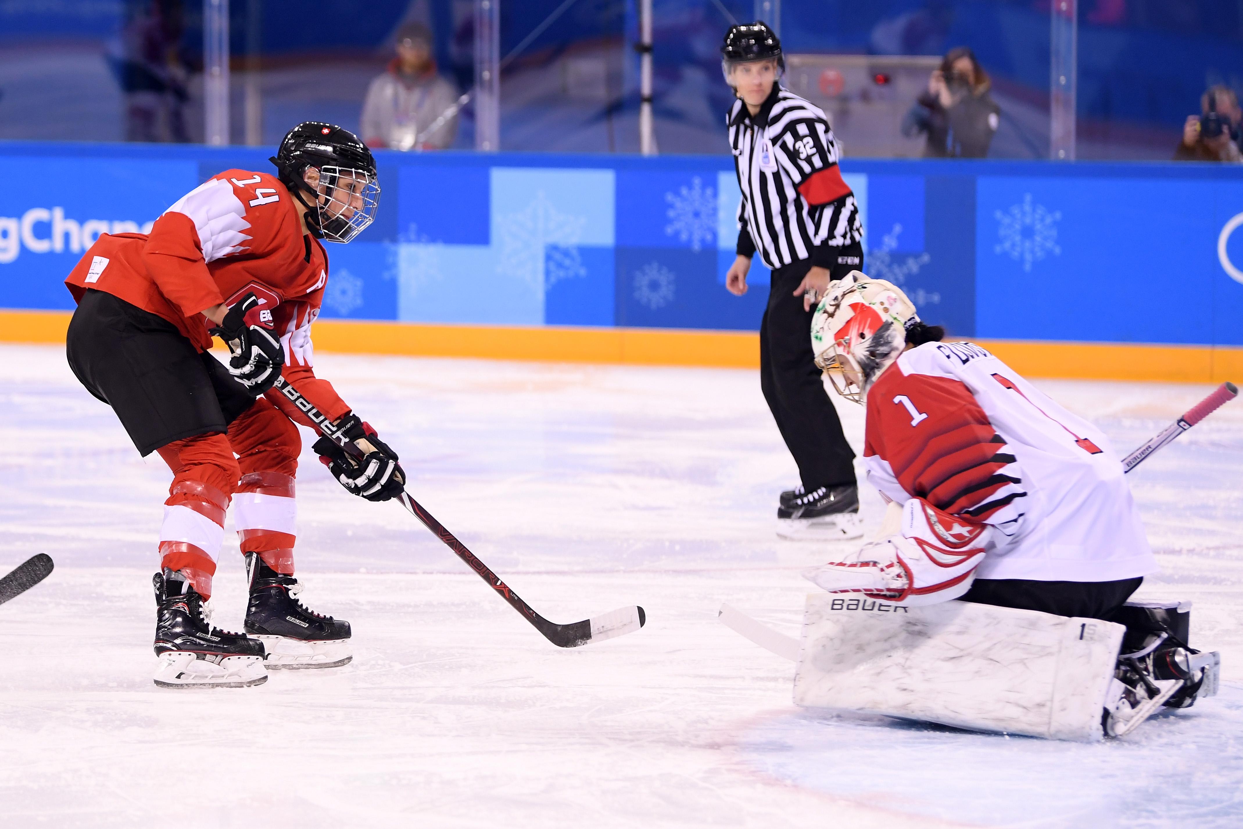 Evelina Raselli #14 of Switzerland shoots and scores against Nana Fujimoto #1 of Japan