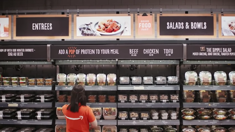 An employee stands in front of a display at an Amazon Go store