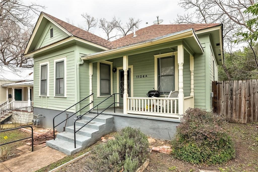Green wooden bungalow with light yellowish trim